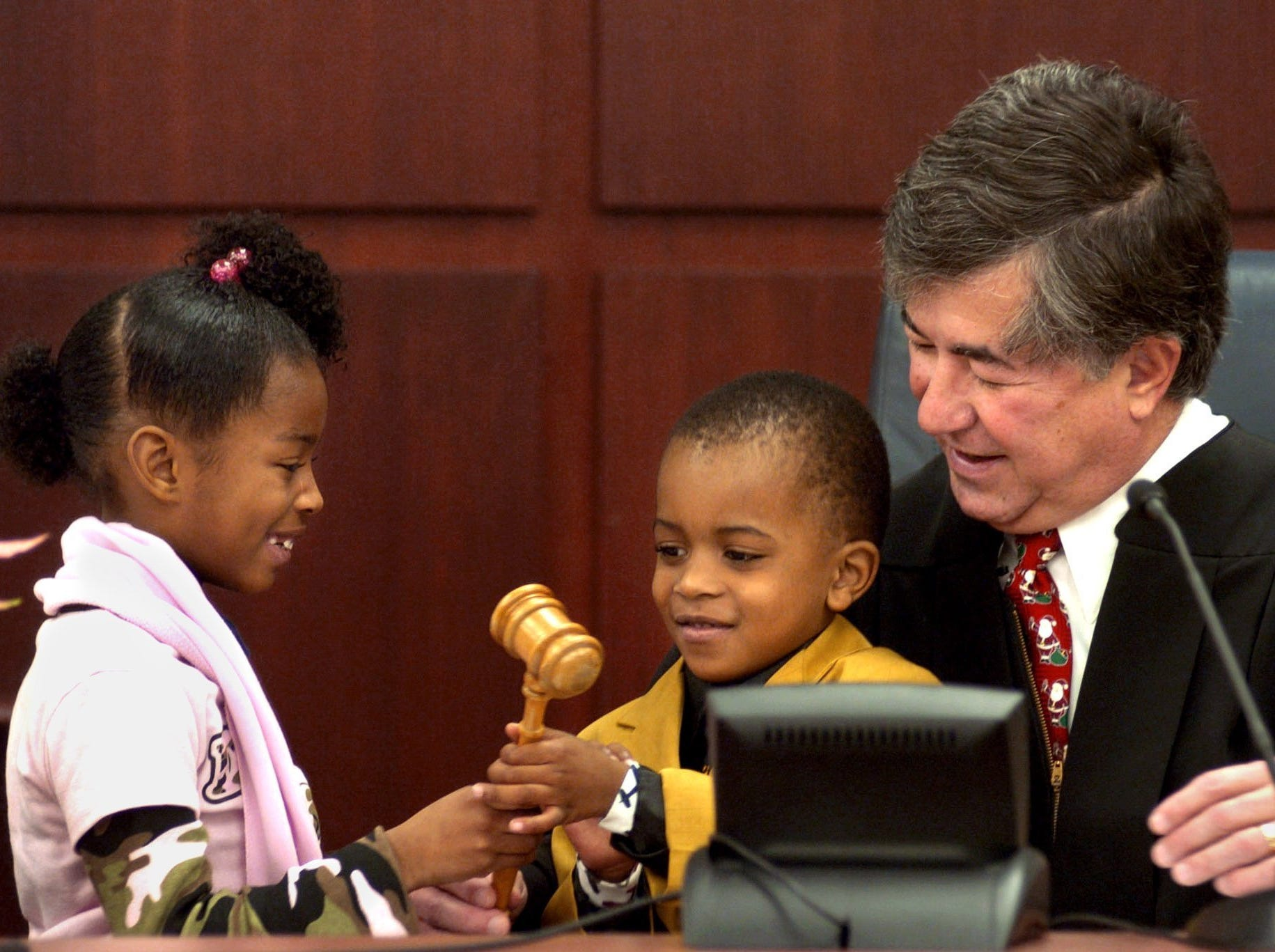 Andrea Verser, left, hands the gavel to her brother Fayshun, 4, after during their adoption proceedings in Judge George Economy's courtroom, Dec. 22, 2004.
