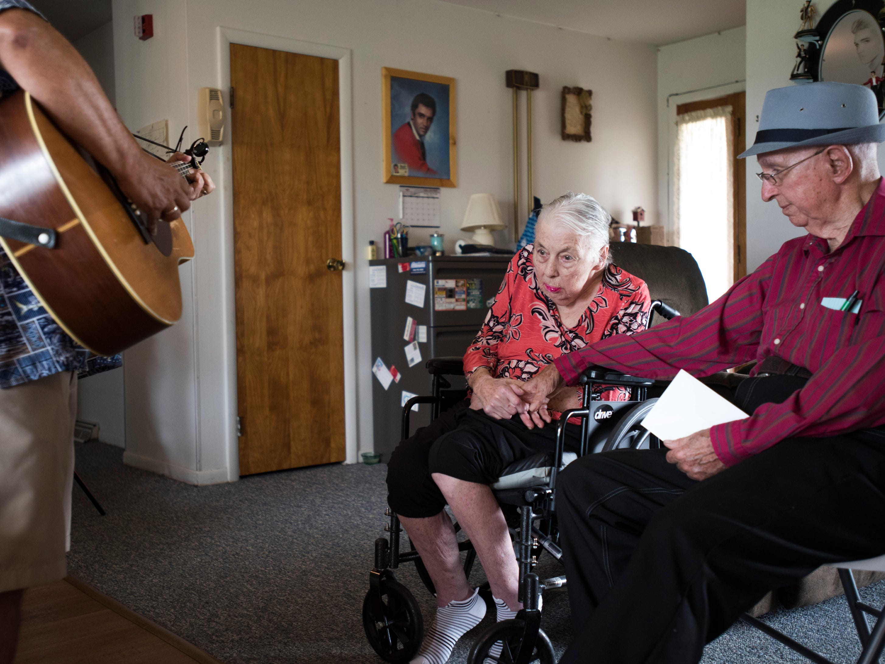 Don West, 90, right, of Eaton Rapids, sits with his wife Jackie, Tuesday afternoon, Aug. 21, 2018, at Golden Days II Adult Foster Care in Charlotte, Michigan during their 64th wedding anniversary party while musician  Dennis Michaels of Lansing plays music for them.  Don has planned the anniversary party for months.