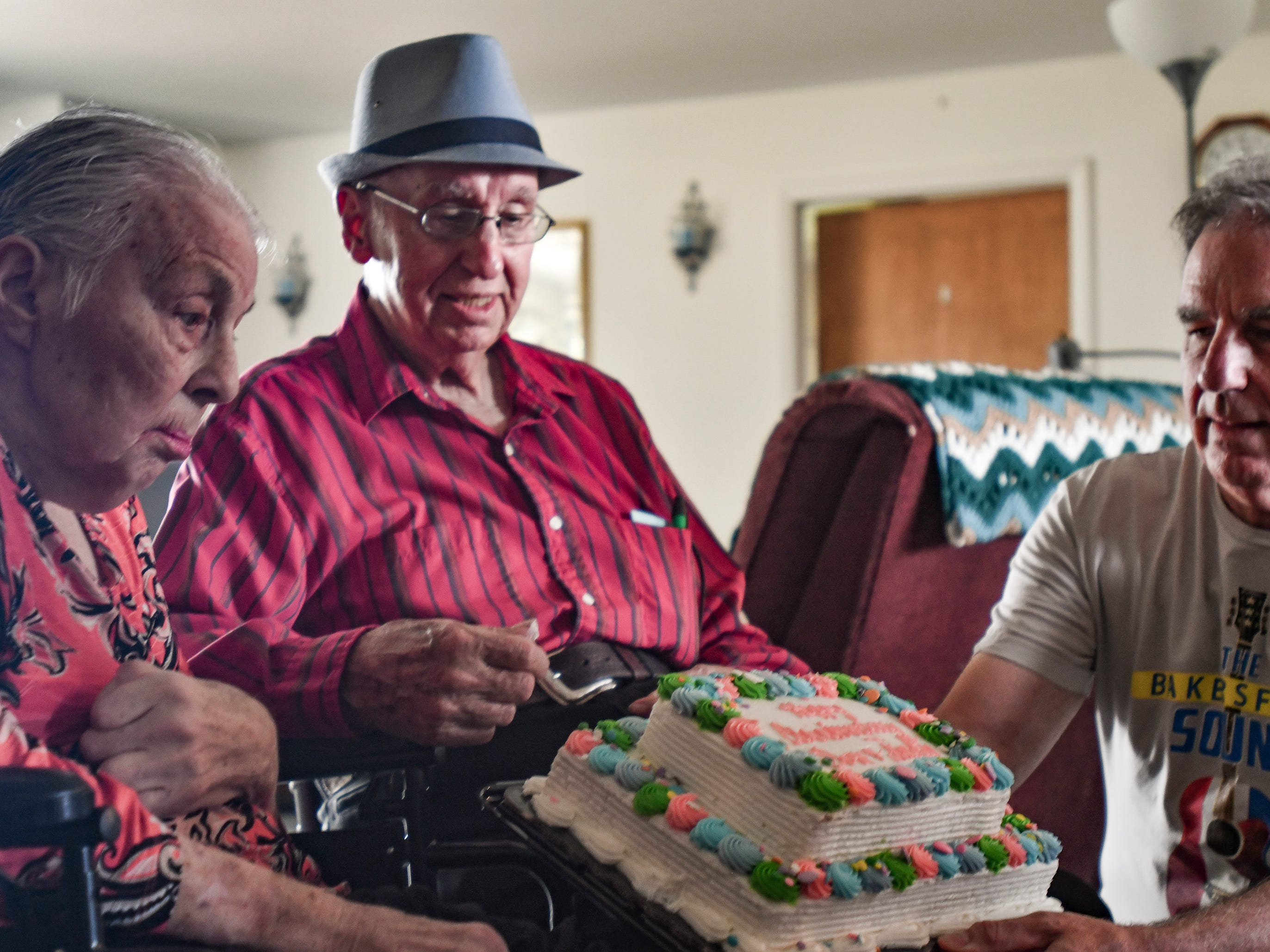 Kerry West, right, of Los Angeles, presents an anniversary cake to his parents Jackie and Don West, Tuesday, Aug. 21, 2018, during their 64th wedding anniversary party in Charlotte.