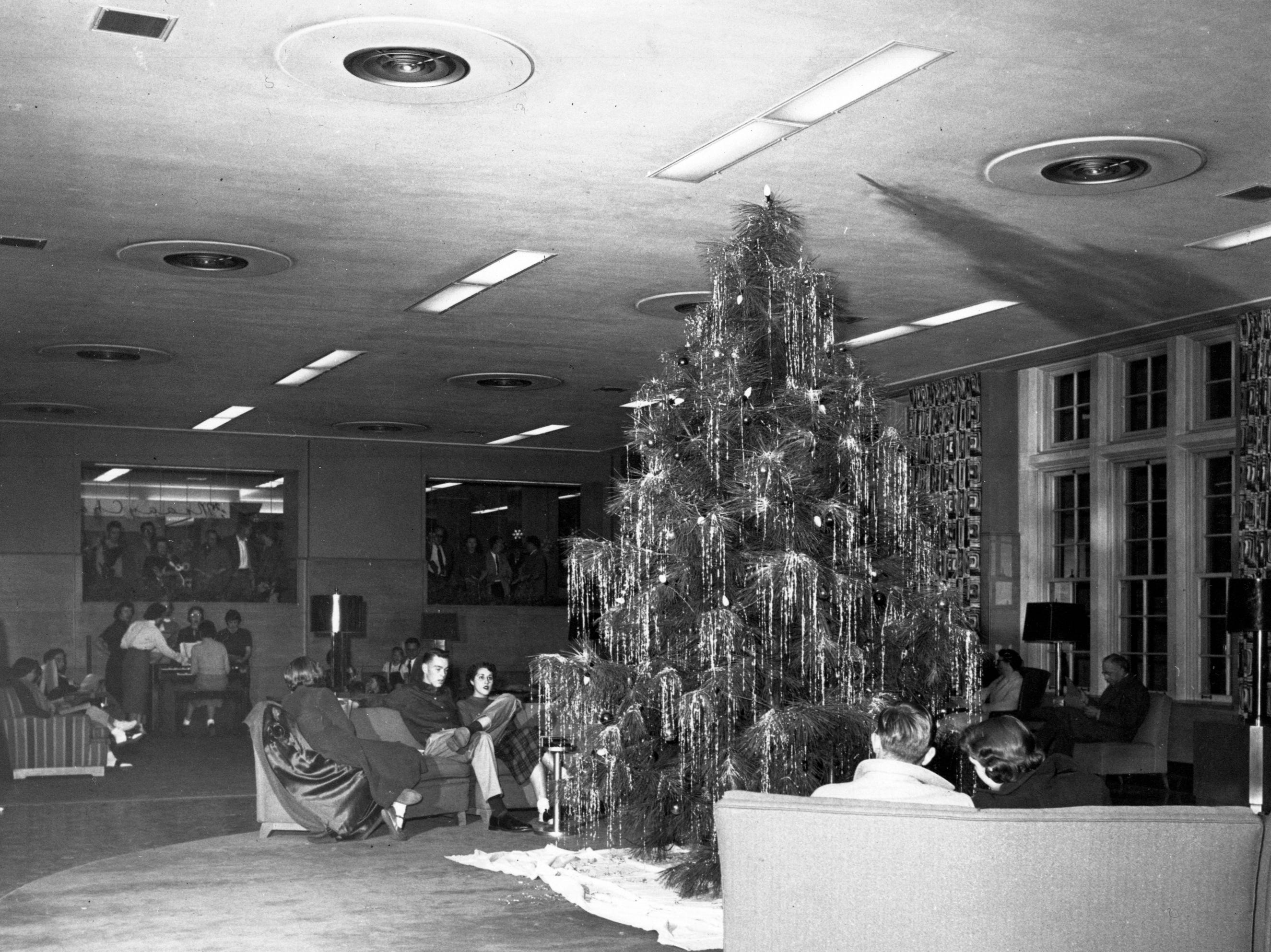 Students sit in the lobby of the MSU Union near a Christmas tree, circa 1958.