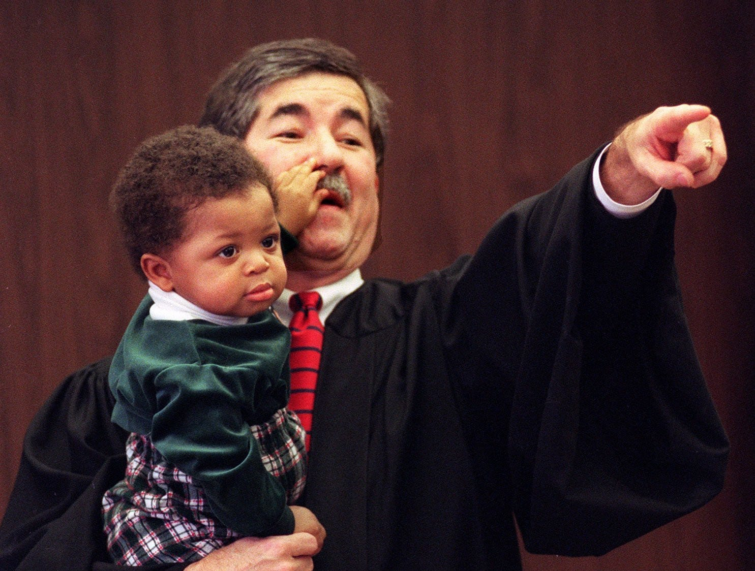 Young Andre Robertson, 10 months, holds on tight to Ingham County Probate Court Judge George Economy's mustache Dec.23, 1997, as Economy points out Andre's now official parents, Alvin and Jacqueline Robertson, after adoption proceedings in Economy's courtroom.