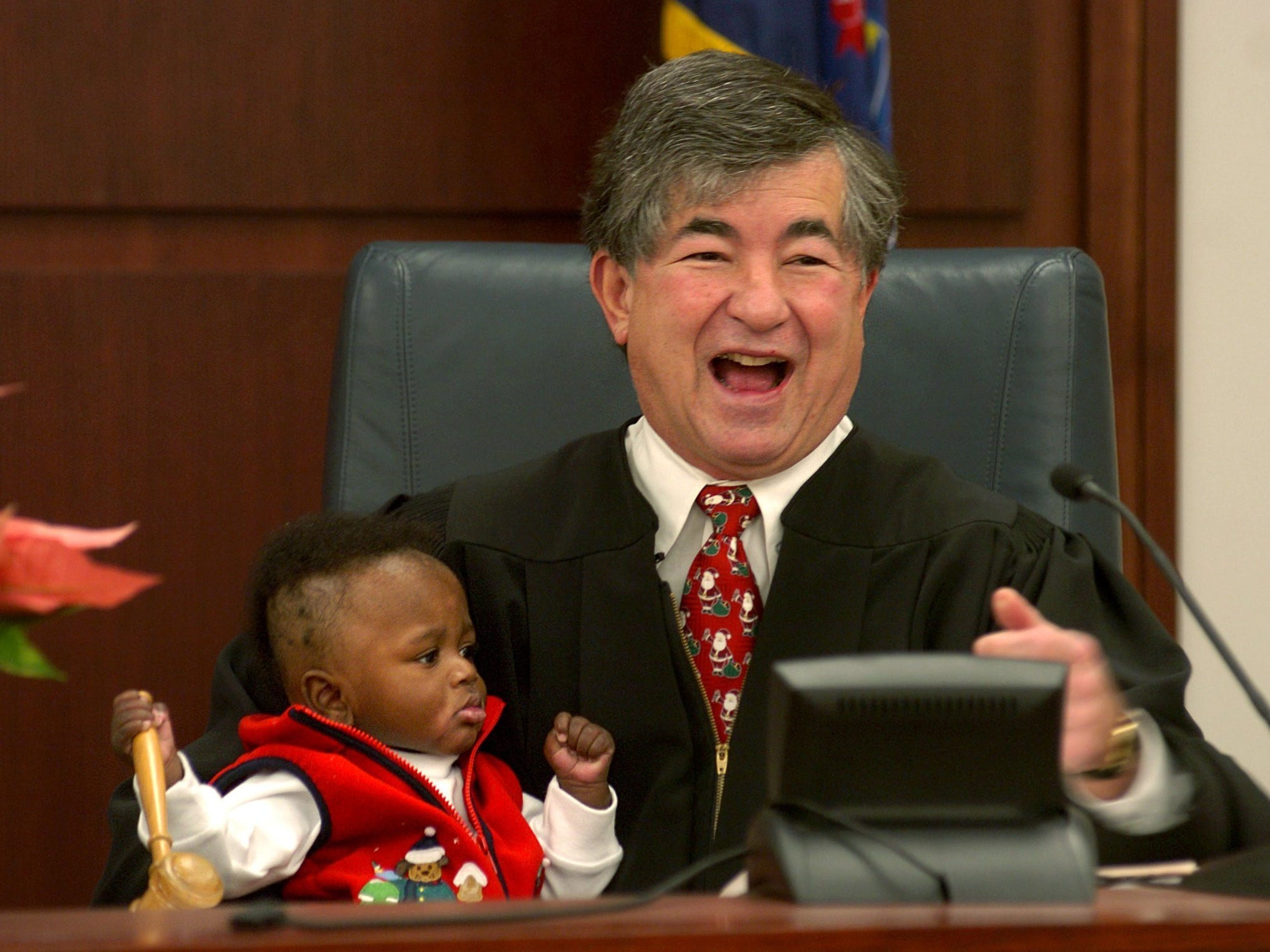 Judge George Economy laughs after handing the gavel to Robert Lamb, 6 months, during his adoption proceedings Dec. 22, 2004. Robert was adopted by Michael and Holly Lamb.
