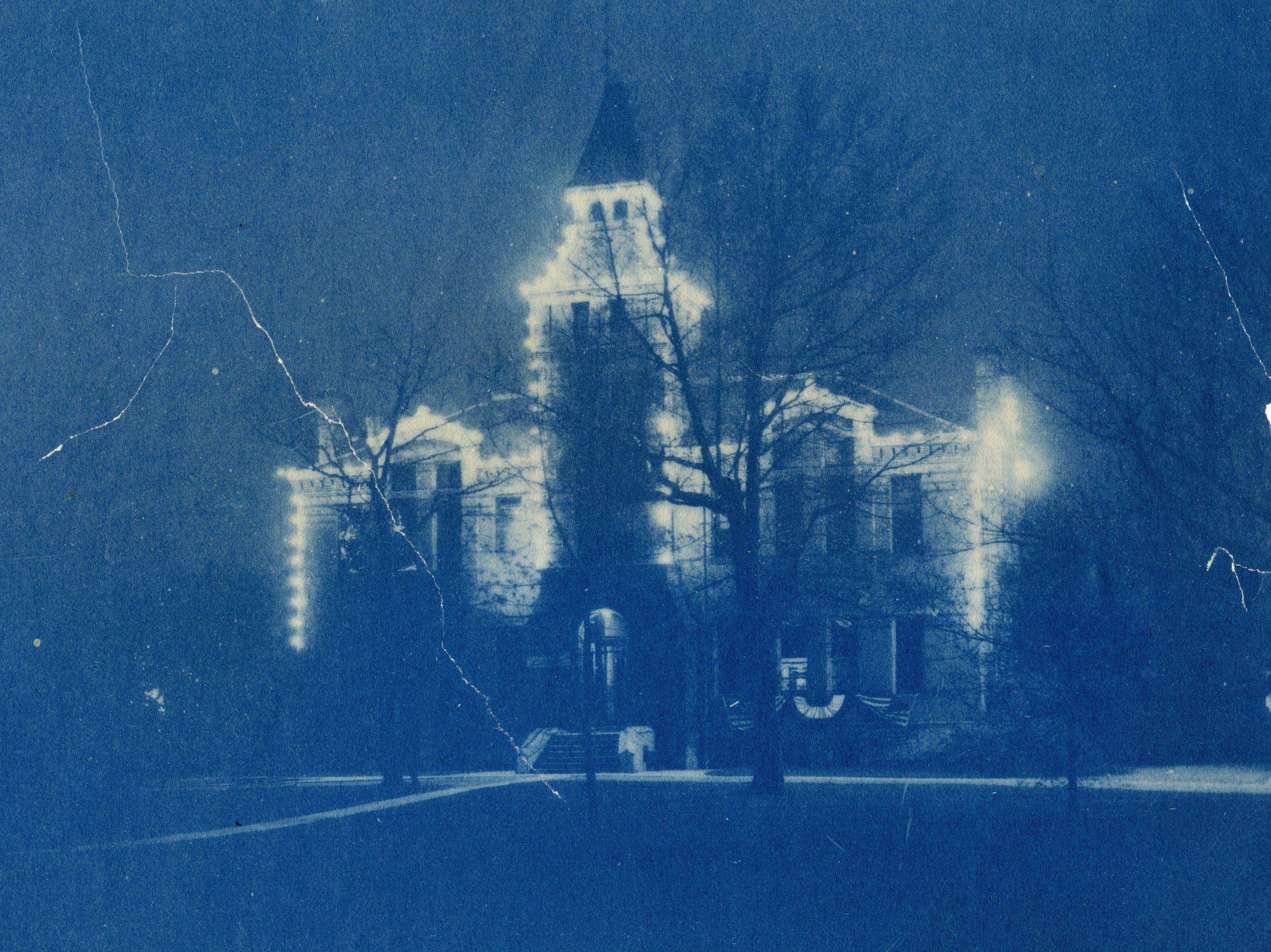 Cyanotype photograph of Linton Hall lit up at night. The building has been decorated for lights, presumably for Christmas, circa 1910.