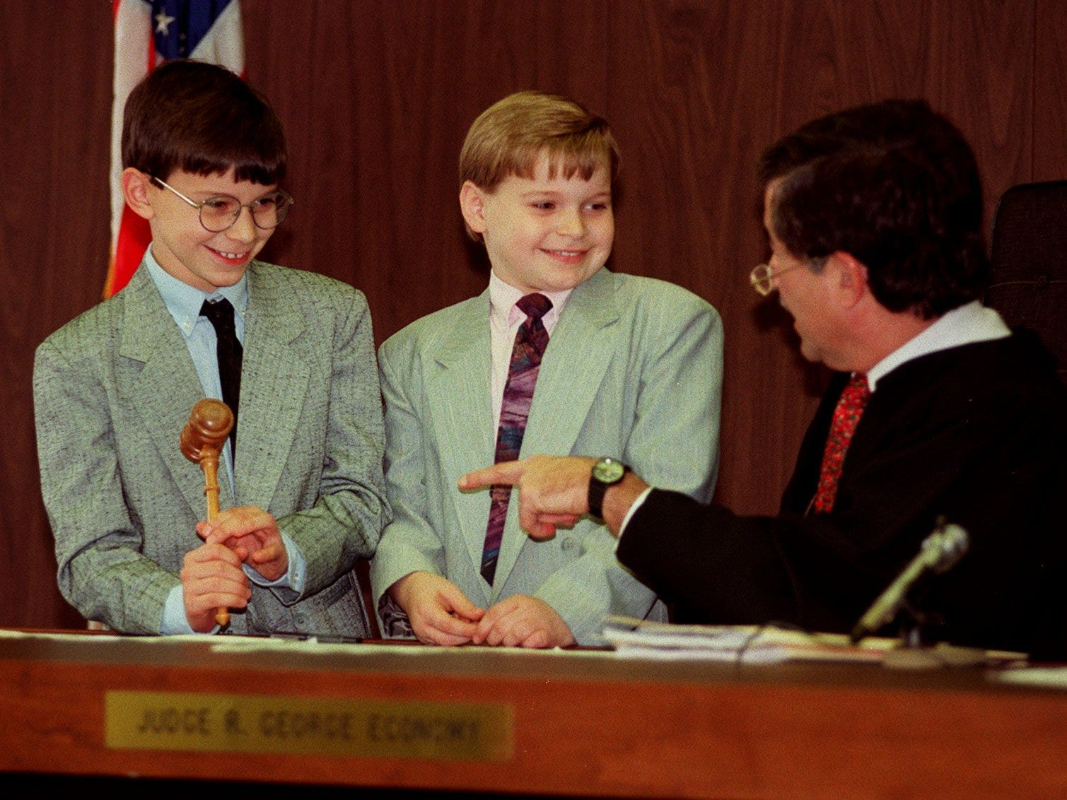 Brothers Joseph Lewis, 9, left, and Anthony Lewis, 8, of Lansing speak with Ingham County Probate Court Judge R. George Economy during their adoption hearing, Dec. 22, 1995. Each boy used the Judge's gavel to officially signify the other's adoption.