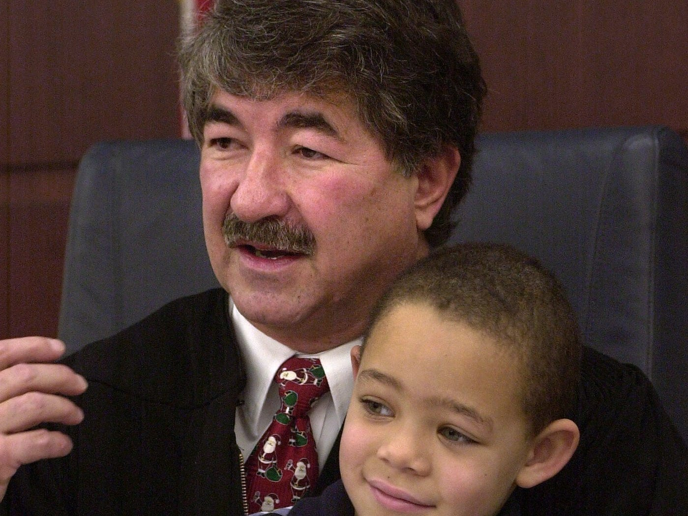 Ty Anthany Adams Allen, 5, is held by Probate Judge George Economy as Ty waits to waits to pound the gavel to finalize his parental adoption by his grandmother, Susan Allen, in Economy's courtroom Dec. 20, 2002.