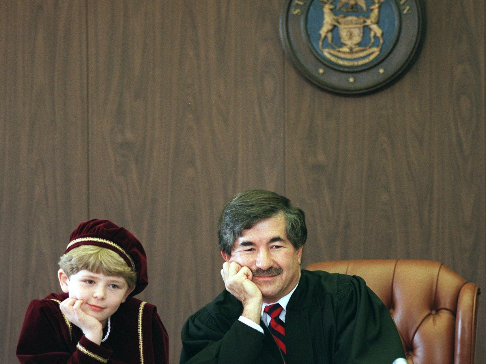 Melissa Bartels, 8, of Haslett and Judge George Economy sit together at the judge's bench during the 11th Annual Christmas Adoptions at the Ingham County Probate and Juvenile Court on Dec. 23, 1998.