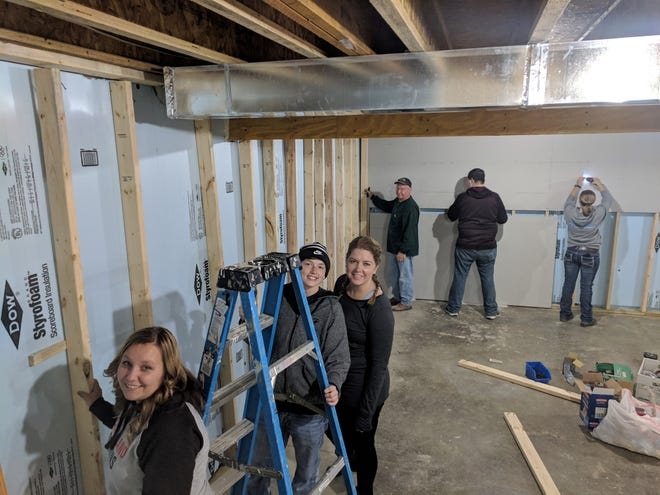 Members of the Marion Technical College sorority Phi Theta Kappa with their advisor Andrew Hand help with home construction.