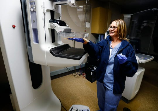 Methodist South Hospital mammogram technician Kelli Webb cleans the hospital's new 3-D screening machine, which has to reduce the number of false-positive screenings.