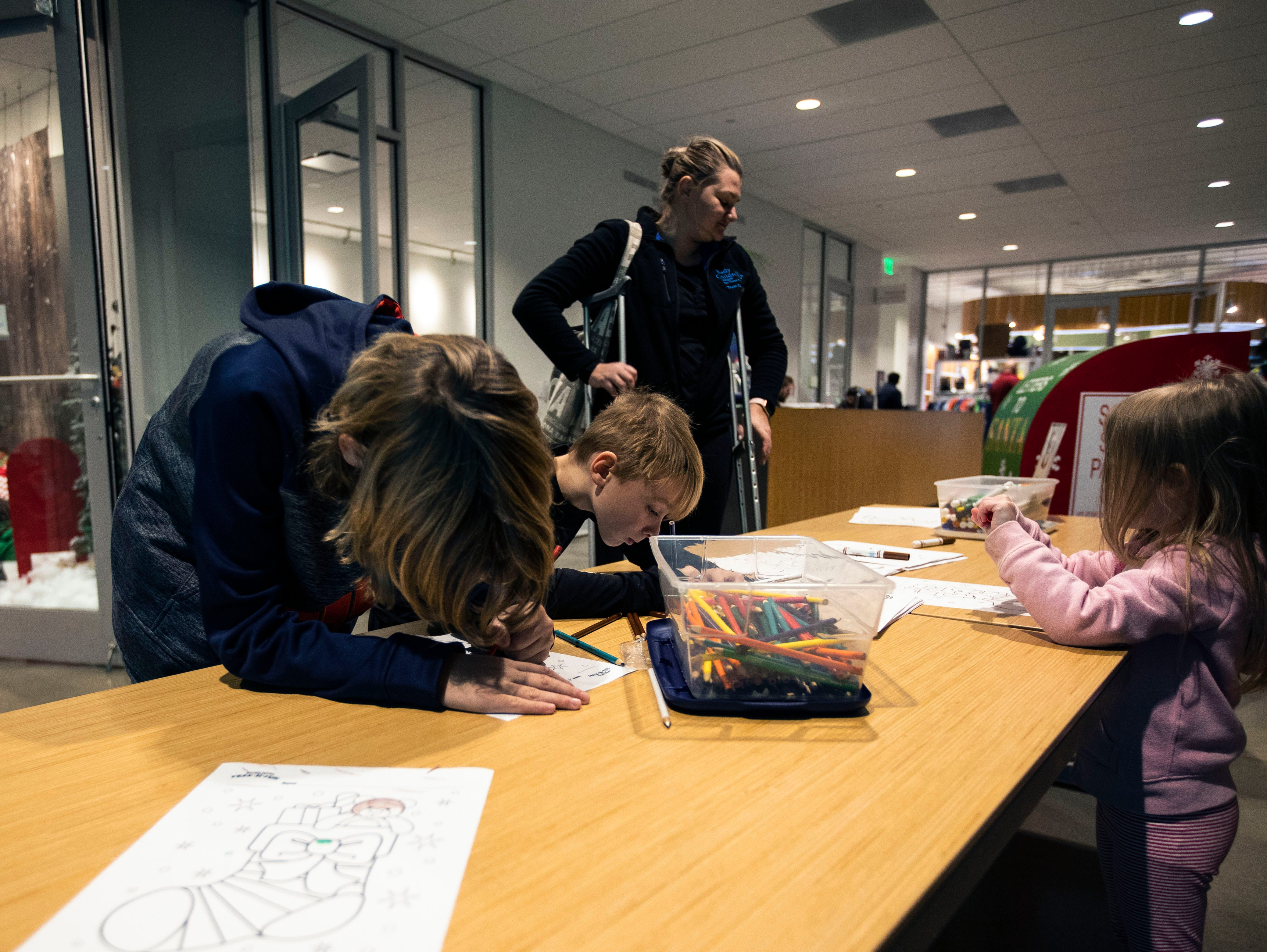 Children color and write letters to Santa at the Starry Nights, annual drive-through light display at Shelby Farms, features walking trails of lights and a drive-through display.
