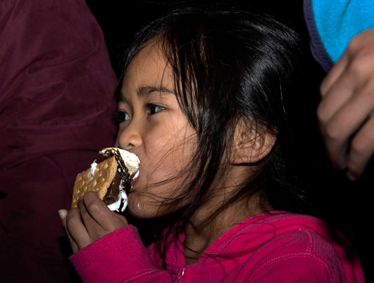 Angelina Siv eats a s'more by the fire at the Starry Nights, annual drive-through light display at Shelby Farms, features walking trails of lights and a drive-through display.