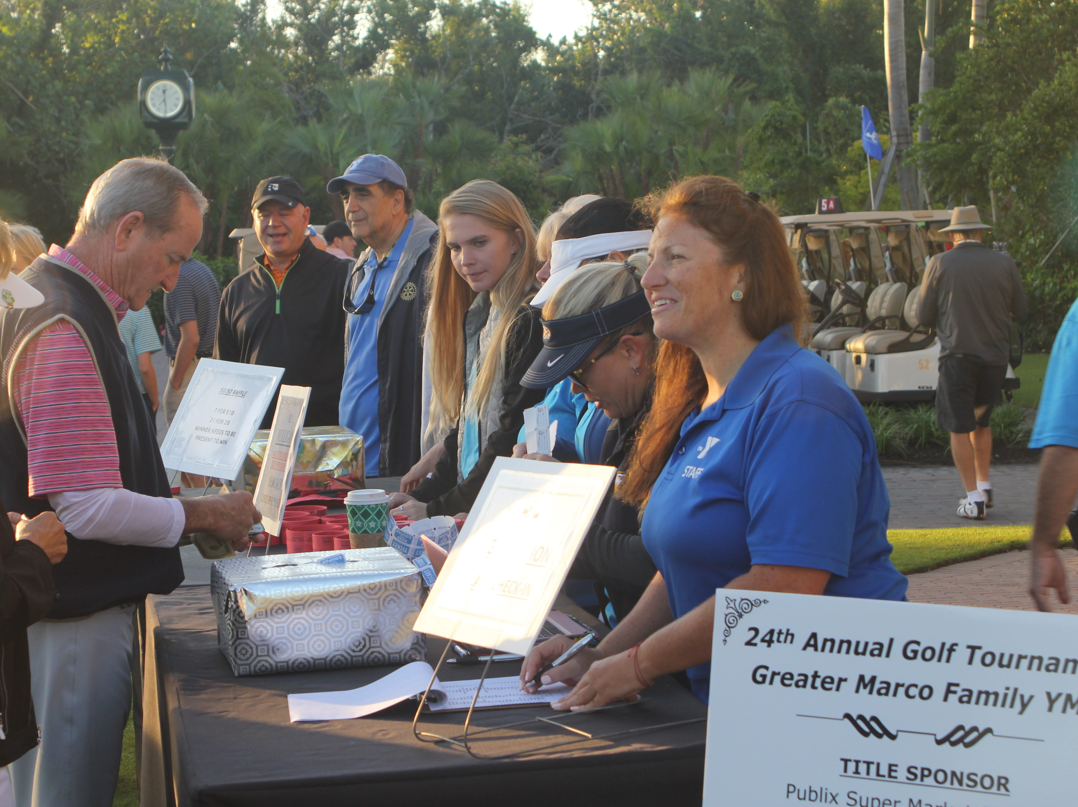 A golfer goes through the check-in procedure before the start of the tournament.