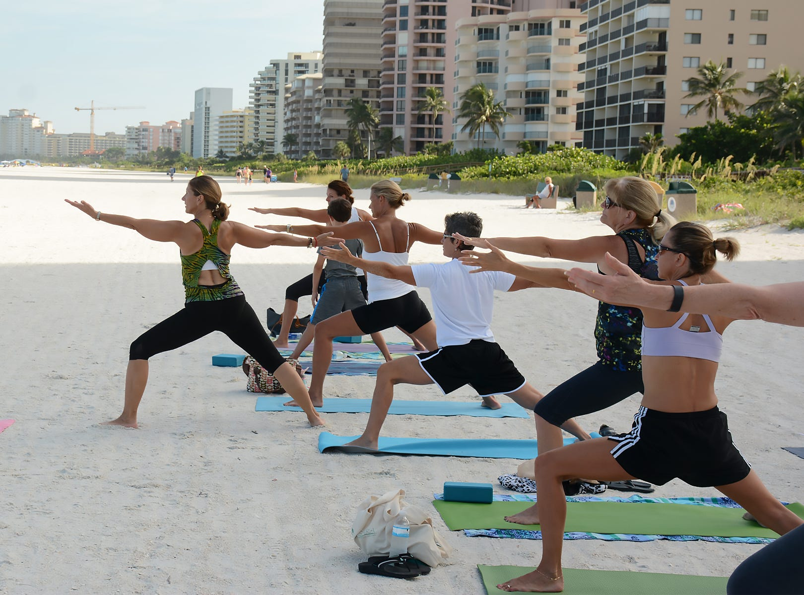 Instructor Laurie Kasperbauer leads a morning class in the warrior pose in this file photo. Marco Island Yoga and Revival Yoga Fitness Studio will join together in a yoga class to raise funds for victims of the shooting at a Tallahassee yoga studio.