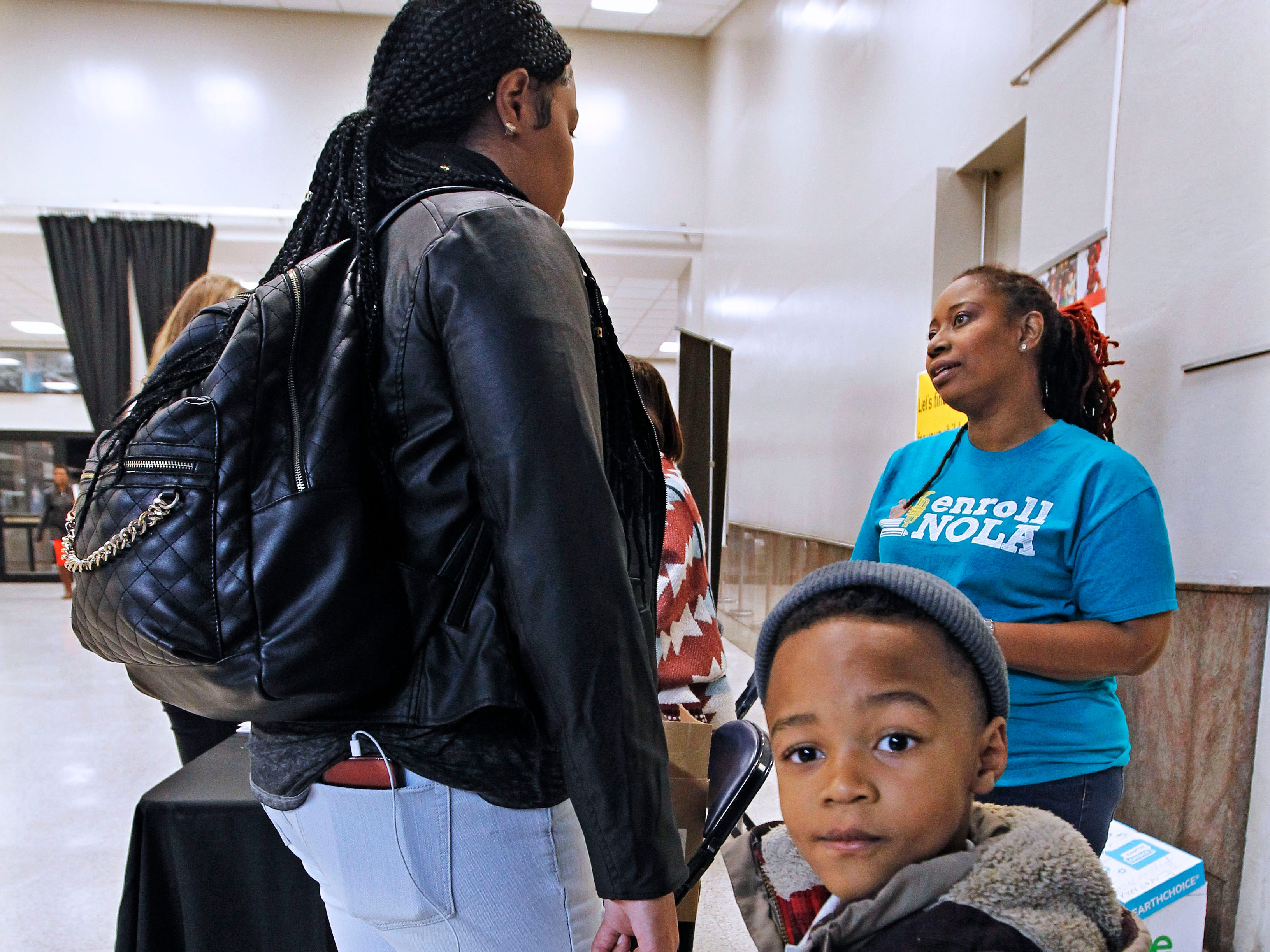 Marvin R. McCants, Jr., 4, waits with his mother Ebony Watson who talks with a rep from Enroll Nola.