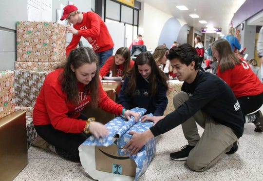Oconomowoc High School DECA students Emma Audley (left) and Jaysin Patel (right) wrap one of the many gifts the school will take to Pershing Elementary School in West Milwaukee.