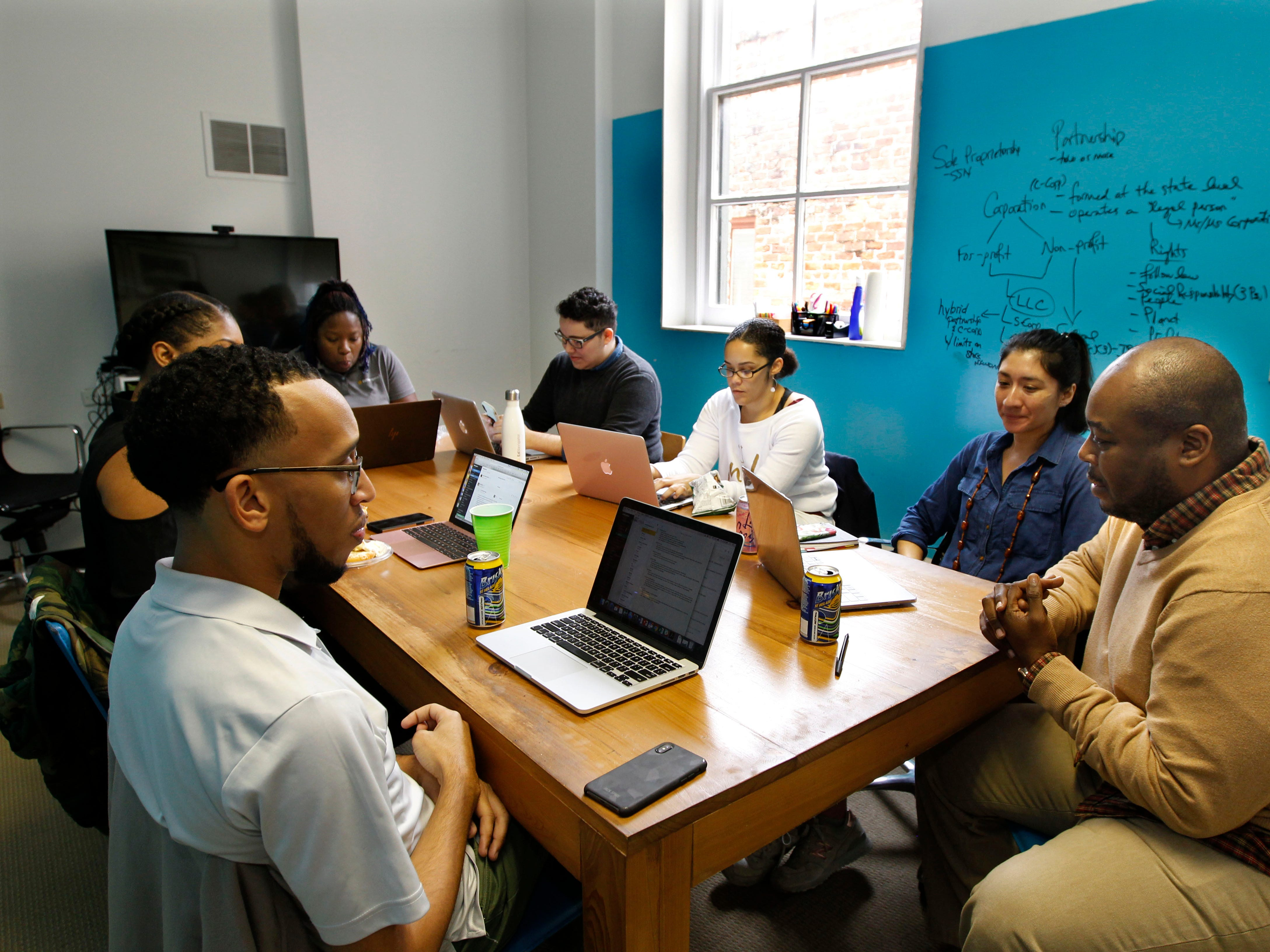 EdNavigators staff (clockwise from left)  Gary Briggs, Whitney Henderson, Rameisha Johnson,  Ileana Ortiz, Summer Duperon, Caroline Cahuantzi, and Ruben Johnson gather for a weekly meeting. EdNavigators was founded to offer family-friendly guidance on education options.