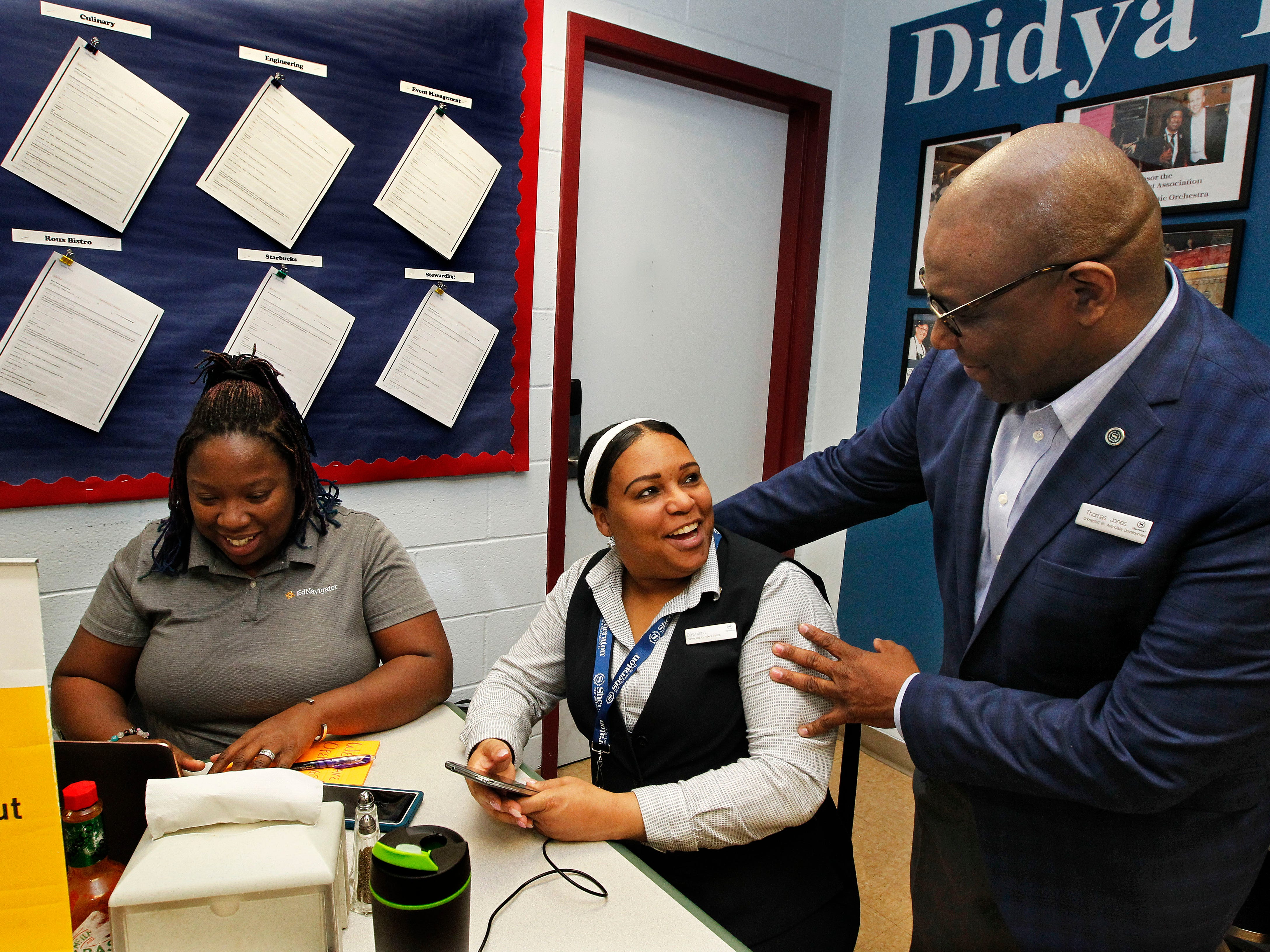 Rameisha Johnson (from left) of EdNavigator with client Dawnisha Norris, and Thomas Jones, Area Director of Human Resources for Starwood Hotels, drops in on Johnson's meeting with Norris in New Orleans. Norris has been in the EdNavigator program for a year. She has eight children.