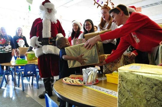 Students at Oconomowoc High School deliver gifts to their adopted school of George Washington Carver Academy in December 2017. They will deliver gifts to Pershing Elementary School Dec. 19 for this year's Adopt A School program.