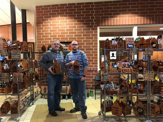 DR Box is owned by Brian and Kim Briesemeister, offers unique wooden beer and wine carriers. Additionally, wooden picture holders and signs are offered. Here, Brian (left) and his son Donald pose during a craft event.