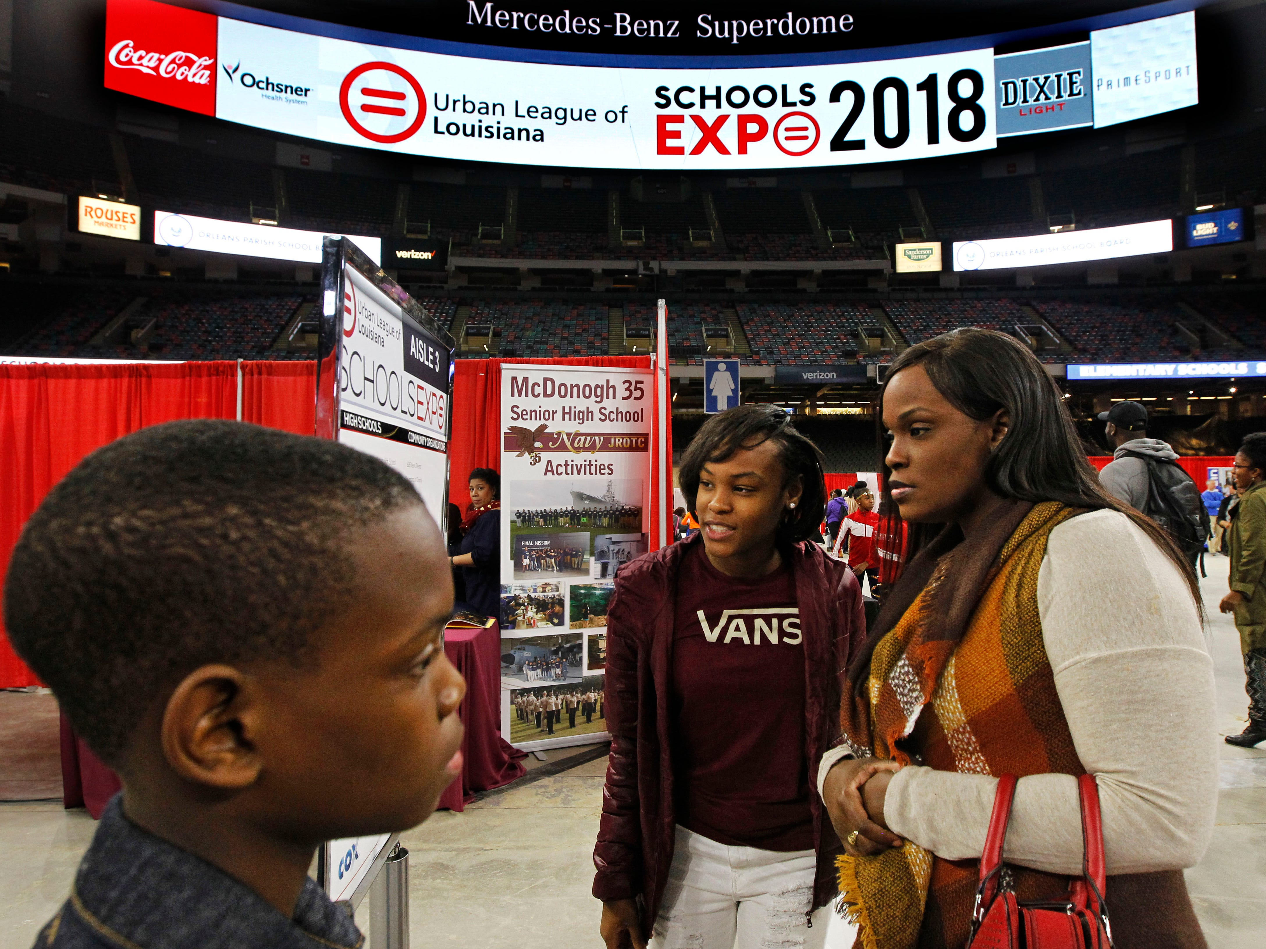 Tamyra Morris (right) looks at the schedule for the Urban League of Schools Expo with her daughter, Takilah Haymond and son  Dan Stevenson at the Mercedes-Benz Superdome in New Orleans. EdNavigator's Gary Briggs suggested Morris attend the event.