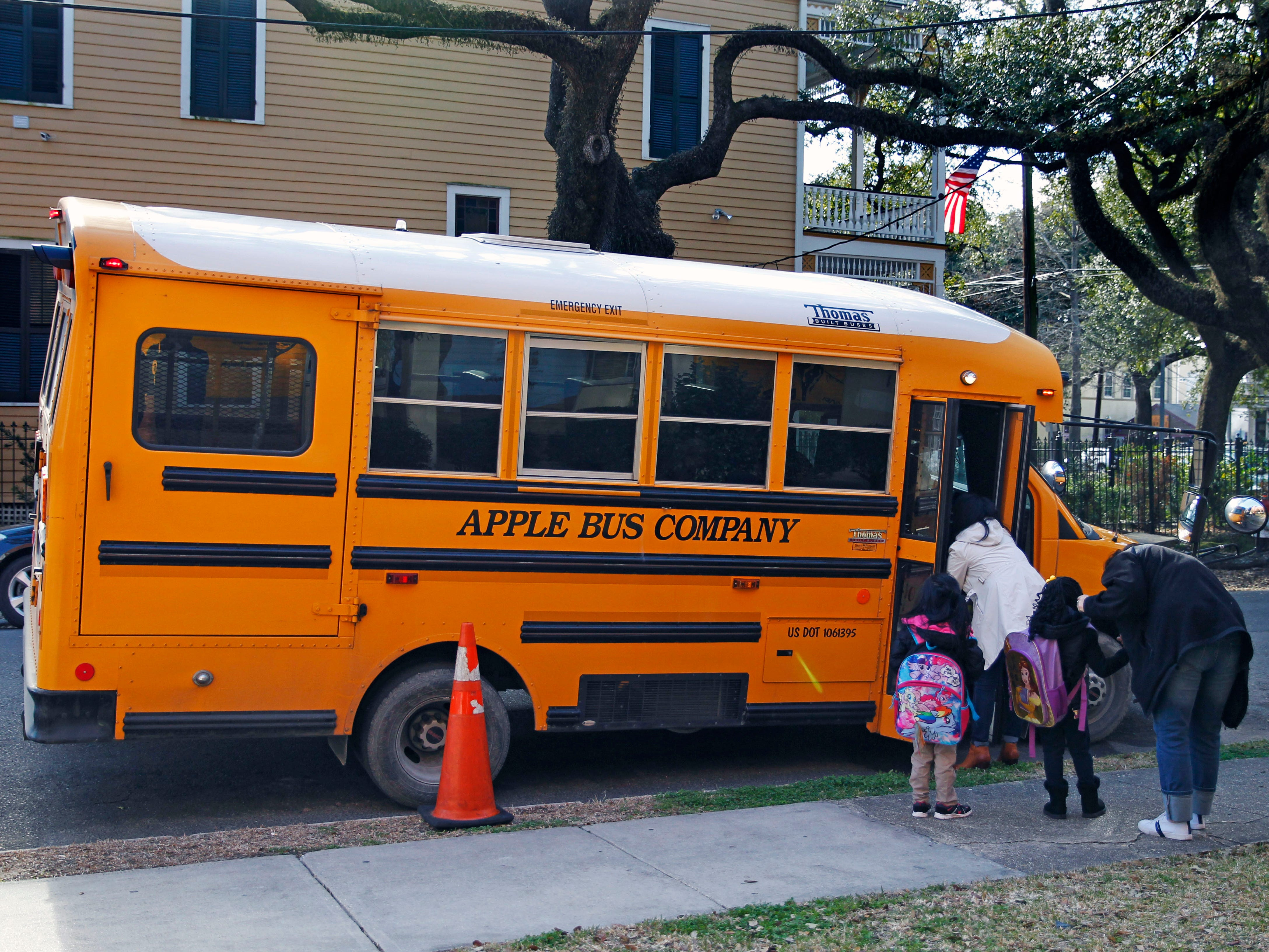 Children board a school bus at the ReNew Ronald E. McNair school in New Orleans at the end of the school day.