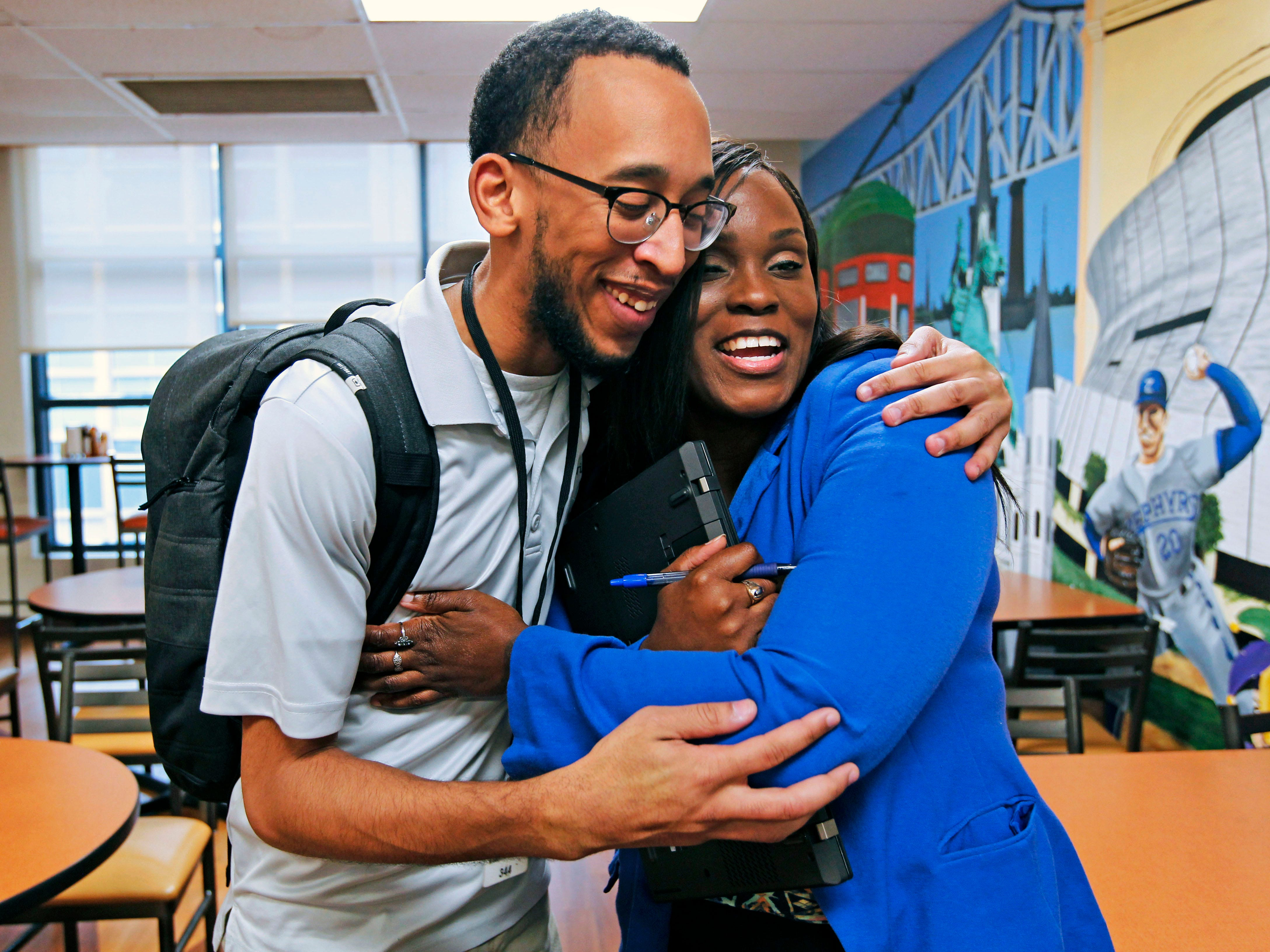 Lead navigator Gary Briggs for EdNavigator (left) gets a hug from from Tamyra Morris, following their weekly meeting.