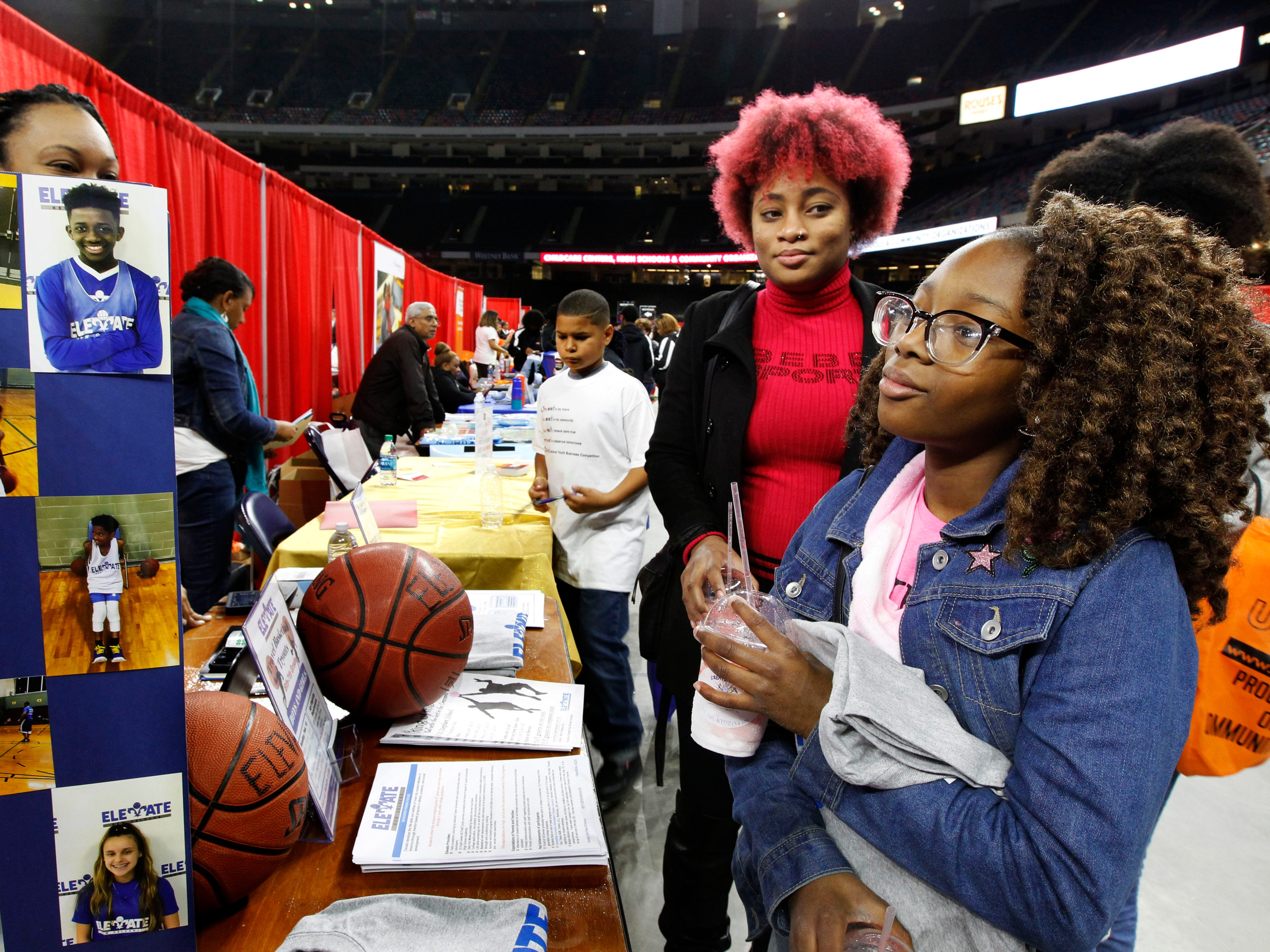 Rhonjae Pomfrey (right), 11, looks over literature at the Elevate table, an after school program, with her mother Rhakeisha Wyre at the Urban League of Schools Expo 2018, at Mercedes-Benz Superdome in New Orleans.