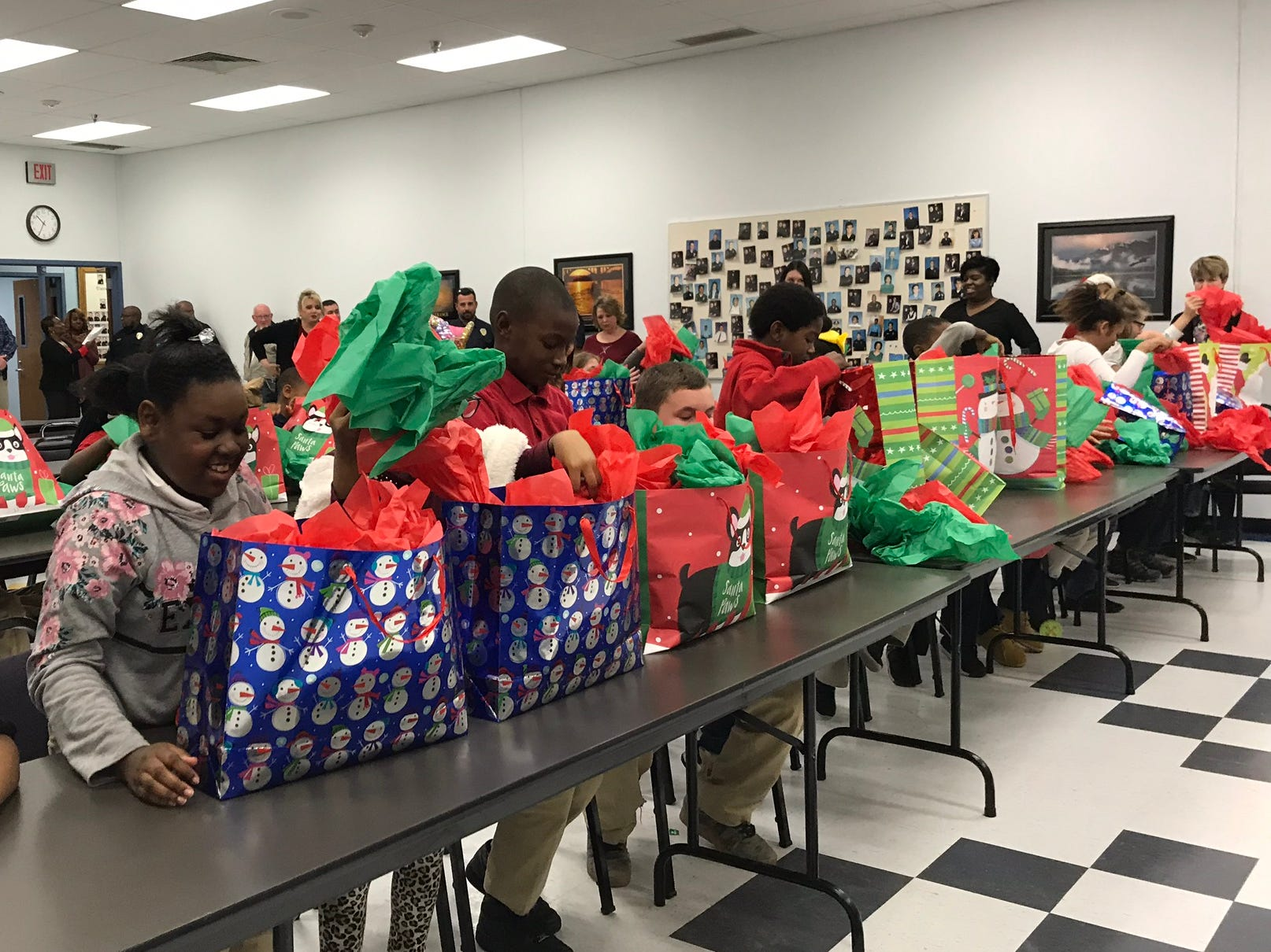 Students from Ouachita Parish Schools open presents of hats and coats at the Public Safety Center Wednesday. The items were provided through a partnership between the MPD, D.A. Steve Tew, T.P. outdoors and the Brad Bell insurance agency