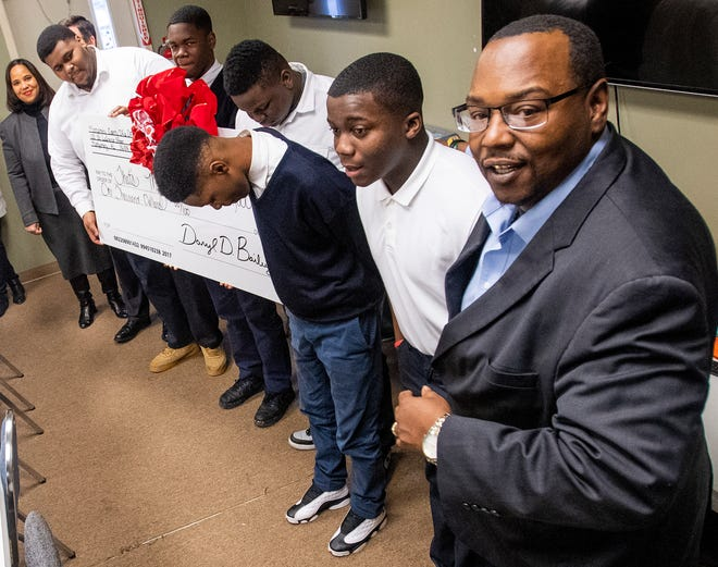 Charles Lee, Executive Director of That's My Child, and youth at the organization receive a check from the Montgomery District Attorney's staff in Montgomery, Ala., on Wednesday December 12, 2018.