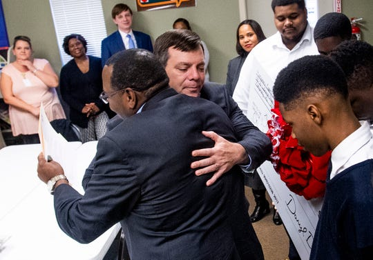 Montgomery District Attorney Daryl Bailey hugs That's My Child Executive Director Charles Lee as the Montgomery District Attorney's staff gives a donation to the facility in Montgomery, Ala., on Wednesday December 12, 2018.