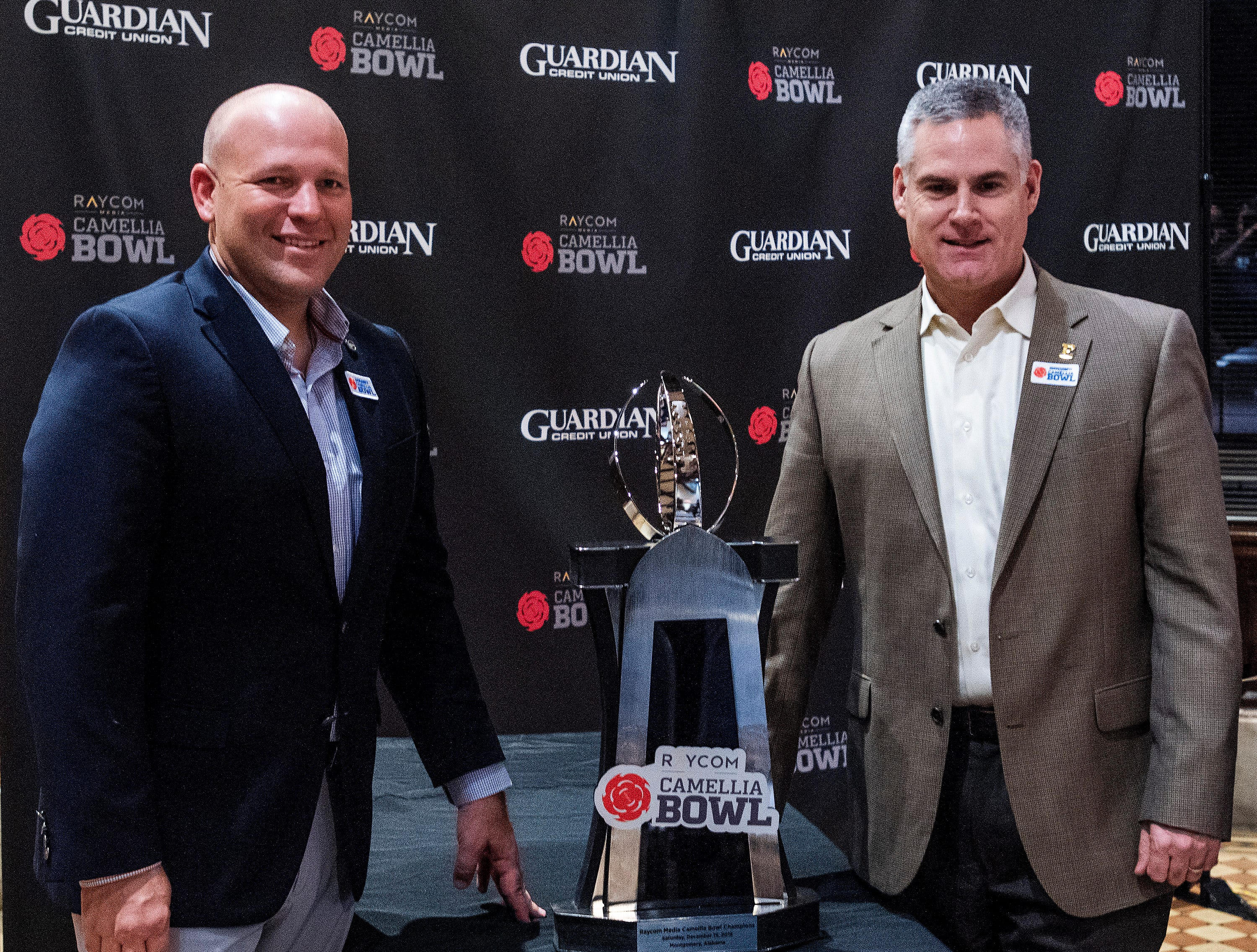 Georgia Southern head coach Chad Lunsford  and Eastern Michigan head coach Chris Creighton pose with the trophy  at the Camellia Bowl Coaches Press Conference in Montgomery, Ala., on Tuesday December 11, 2018.