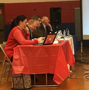 School board members Brittany Bales, Dave Heeter and Jim Williams discuss bonus pay on Tuesday night. Emergency manager Steve Edwards, far right, listens.