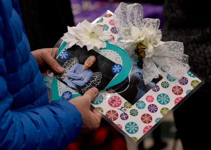 Yun Wang holds ornaments with photos of his dad, Ruxin Wang, at the Metro Police Department's North Precinct on Tuesday, Dec. 11, 2018, in Nashville, Tenn. The police department hosted the Victim Intervention Program event to help families cope during the holidays.