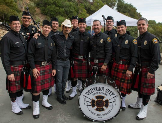 Brad Paisley, in cowboy hat, poses with the Ventura City firefighters pipe and drum band before he plays a benefit show with them May 12, 2018, for victims of California wildfires and mudslides in Santa Barbara.