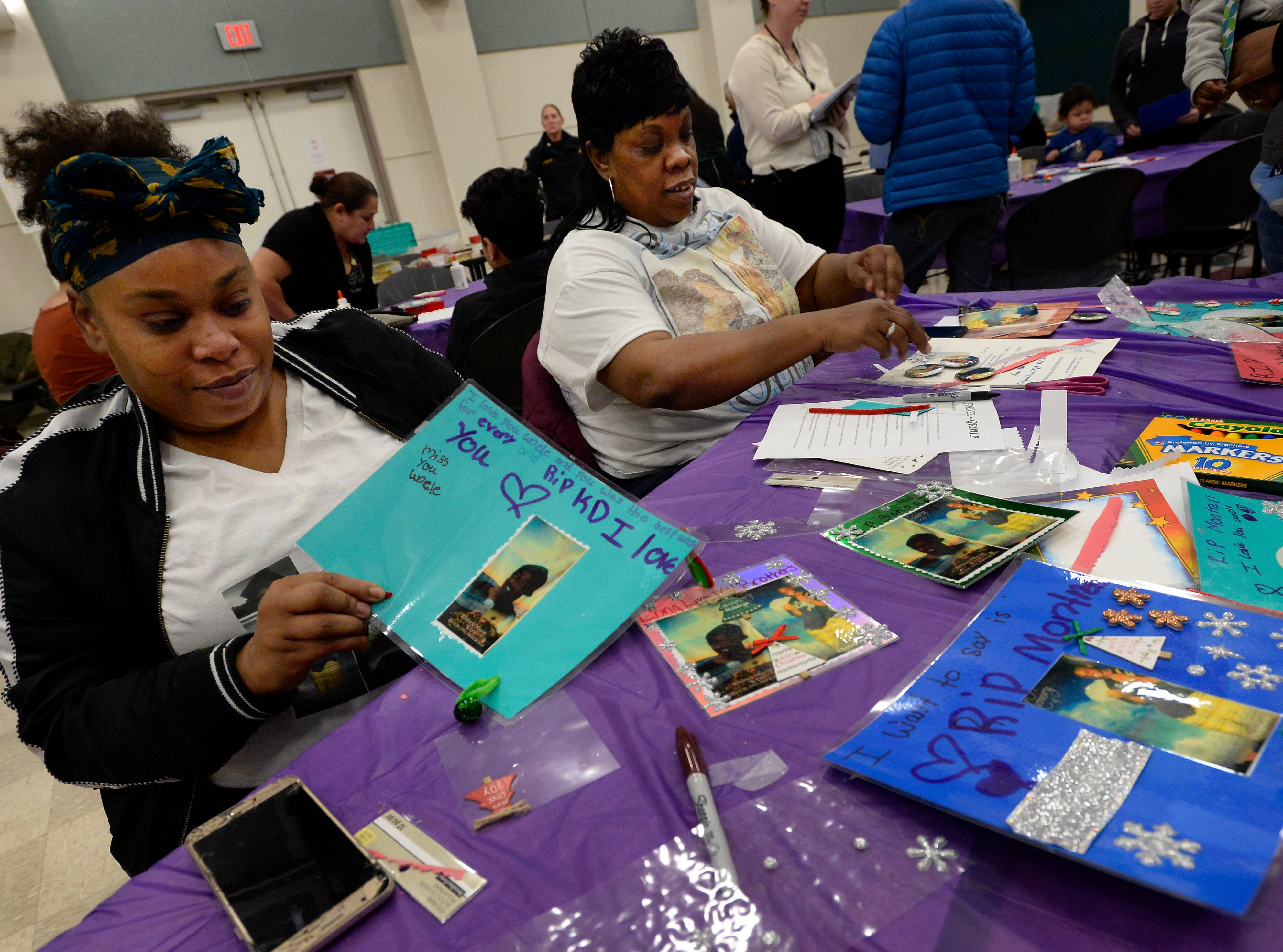Roketa Mason and her mother, Yolanda Mason, make Christmas ornaments at the Metro Police Department's North Precinct on Tuesday, Dec. 11, 2018, in Nashville, Tenn. Yolanda Mason's sons, Montrell Mason and Rodrick Mason were homicide victims. The police department hosted the Victim Intervention Program to help families cope during the holidays.