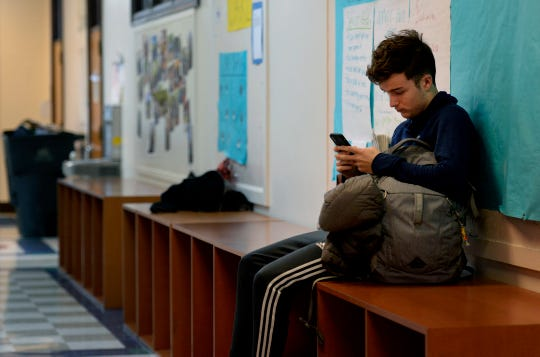 "University School of Nashville student Elias Woolsey uses his cellphone after class in the hallway on Tuesday, Dec. 11, 2018. Teachers have created ""phone home"" spaces to prevent students from using their mobile devices during class."