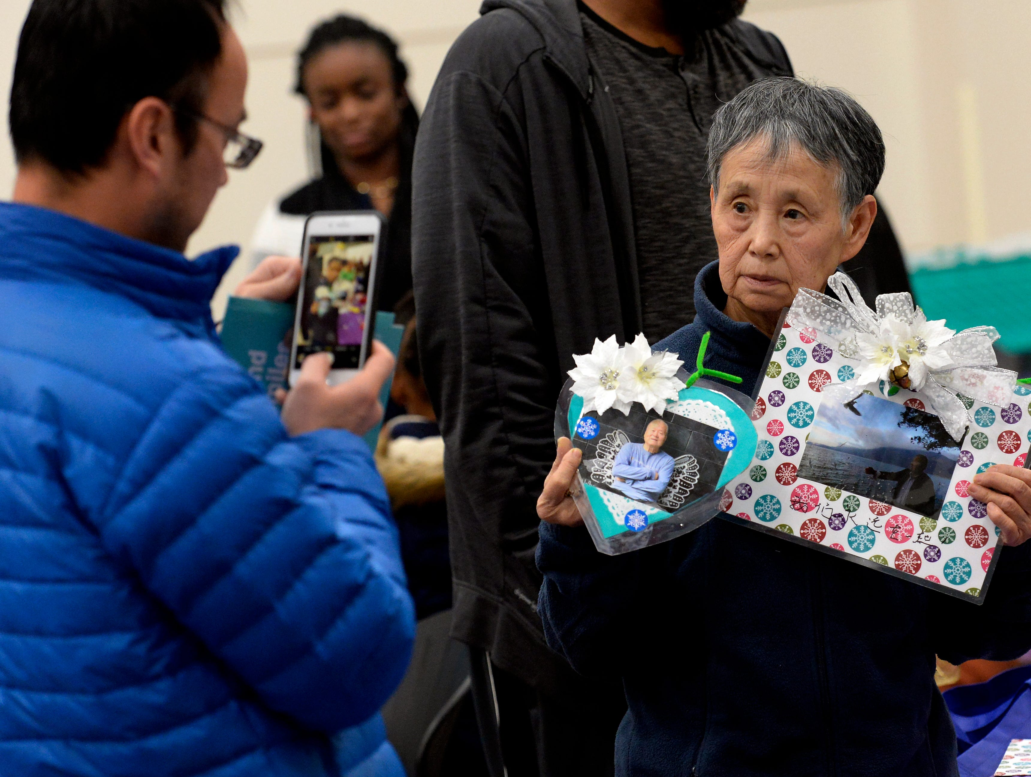 Youg Ling Zhai holds ornaments with photos of her husband, Ruxin Wang, at the Metro Police Department's North Precinct on Tuesday, Dec. 11, 2018, in Nashville, Tenn. Her son, Yun Wang, takes a picture of her during the Victim Intervention Program, which is a community outreach program through the police department.