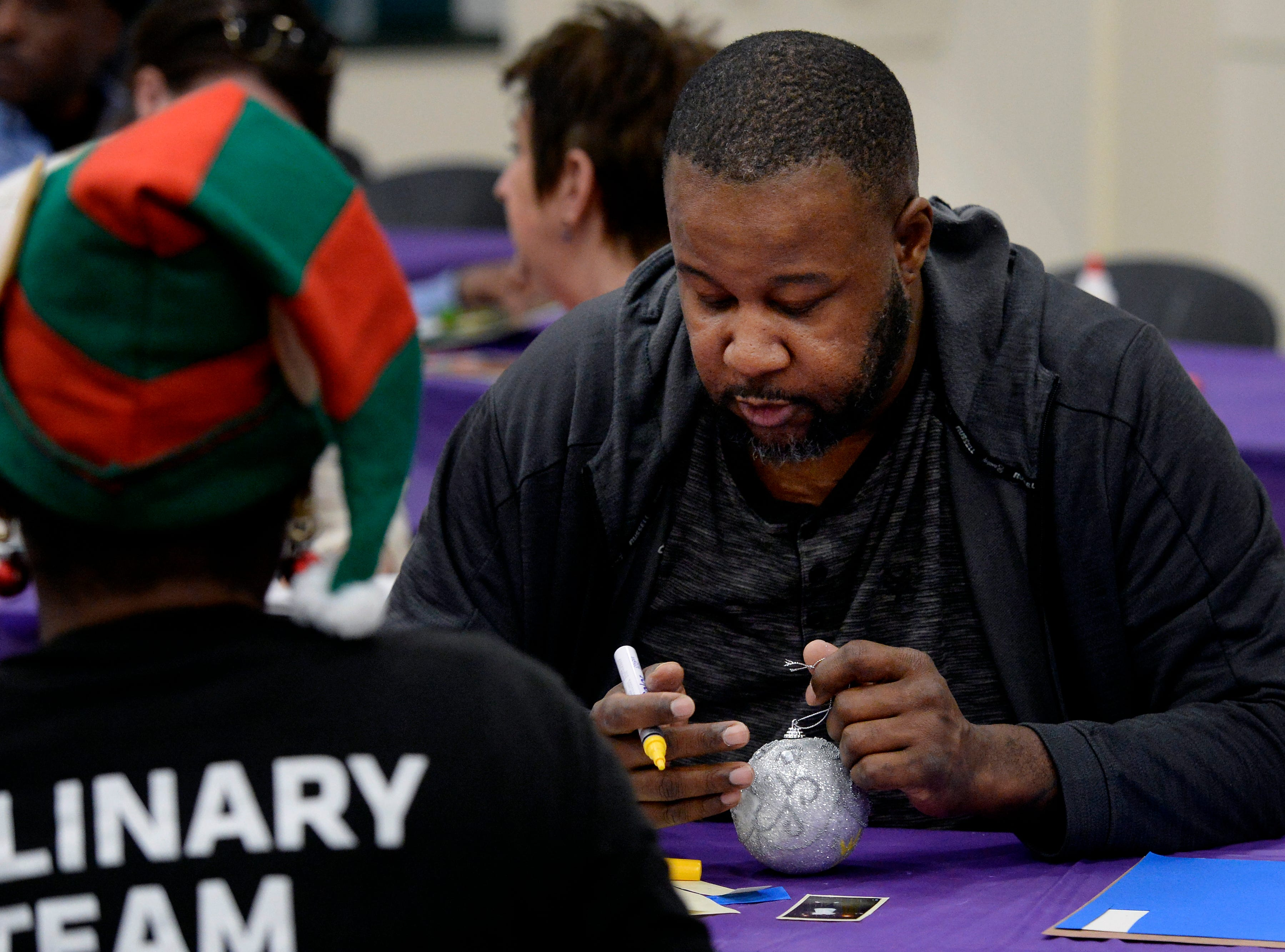 Aland Harris Sr. makes a Christmas ornament in memory of his son, Alando Harris II, at the Metro Police Department's North Precinct on Tuesday, Dec. 11, 2018, in Nashville, Tenn. The Victim Intervention Program is a community outreach program through the police department.