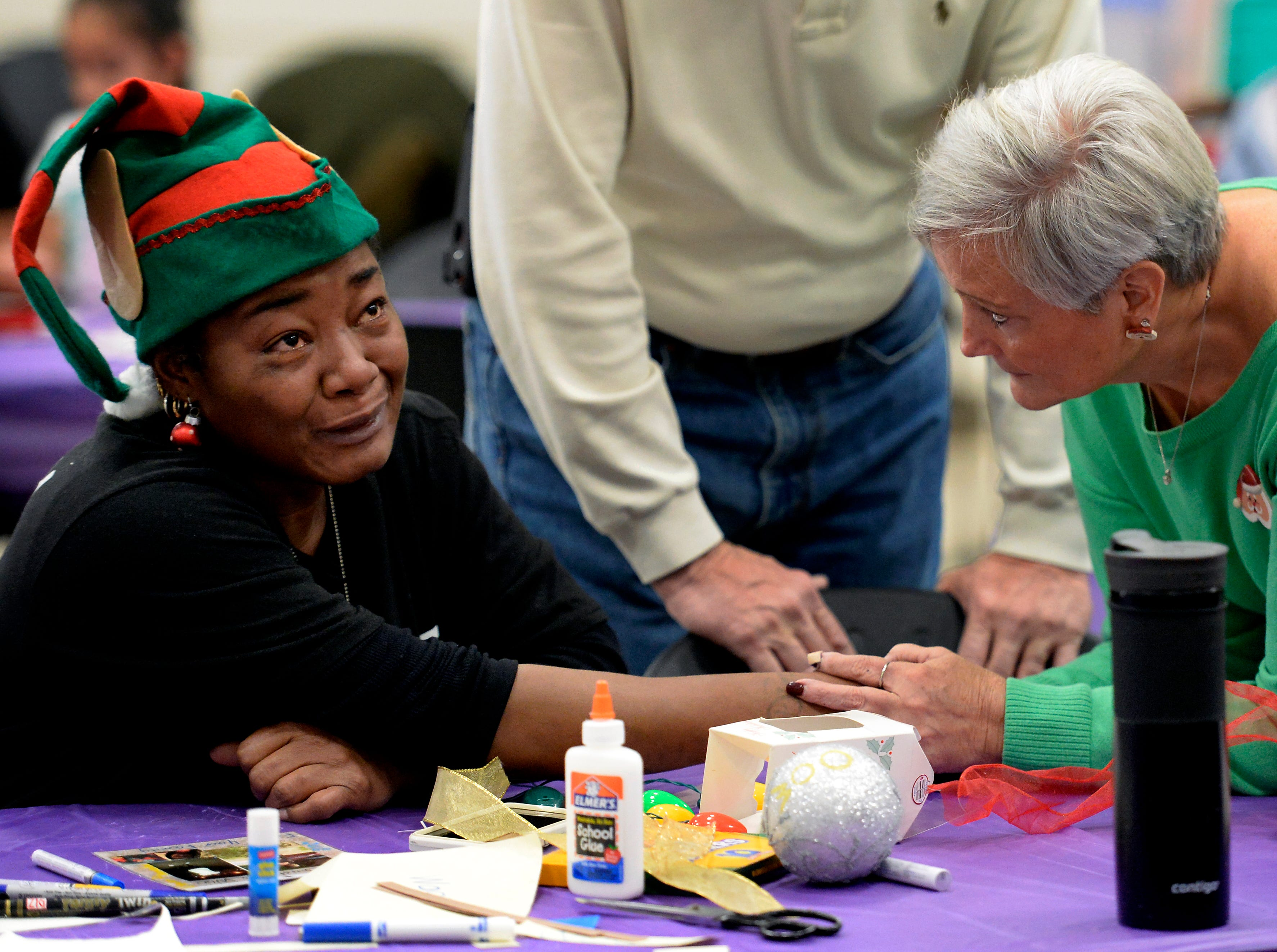Cherrie Anglin is comforted by Judy Davis while making a Christmas ornament in memory of her son, Alando Harris II, at the Metro Police Department's North Precinct on Tuesday, Dec. 11, 2018, in Nashville, Tenn. The Victim Intervention Program is a community outreach program through the police department.