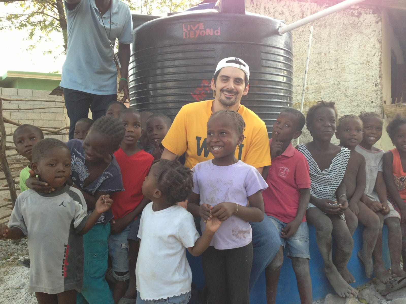 Brad Paisley stands with children in Haiti in front of a new water tank he helped install in February 2013.
