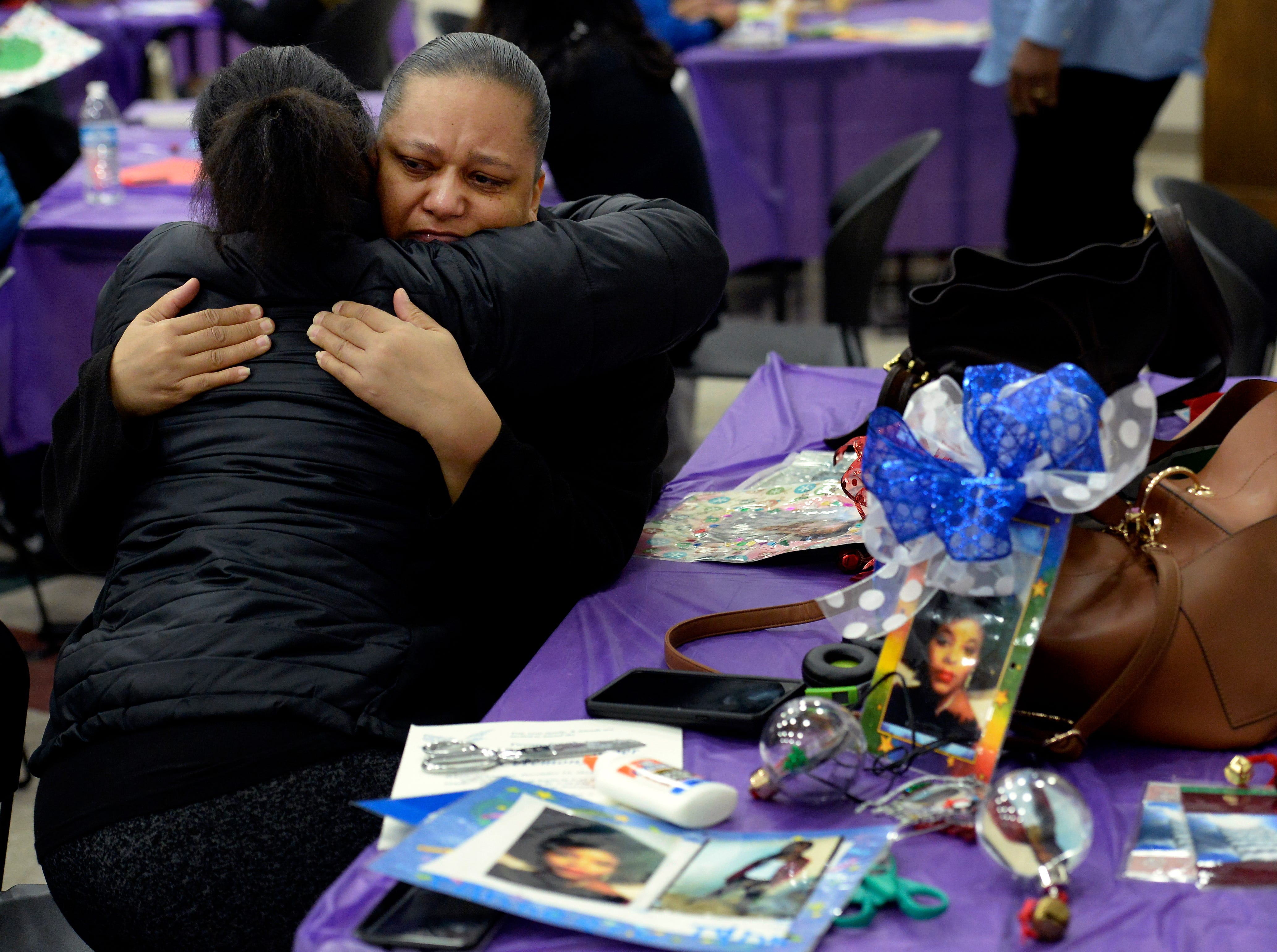 Quiana Hendricks is comforted by Tanesha White while making a Christmas ornament in memory of her son, William Ervin, at the Metro Police Department's North Precinct on Tuesday, Dec. 11, 2018, in Nashville, Tenn. The Victim Intervention Program is a community outreach program through the police department.