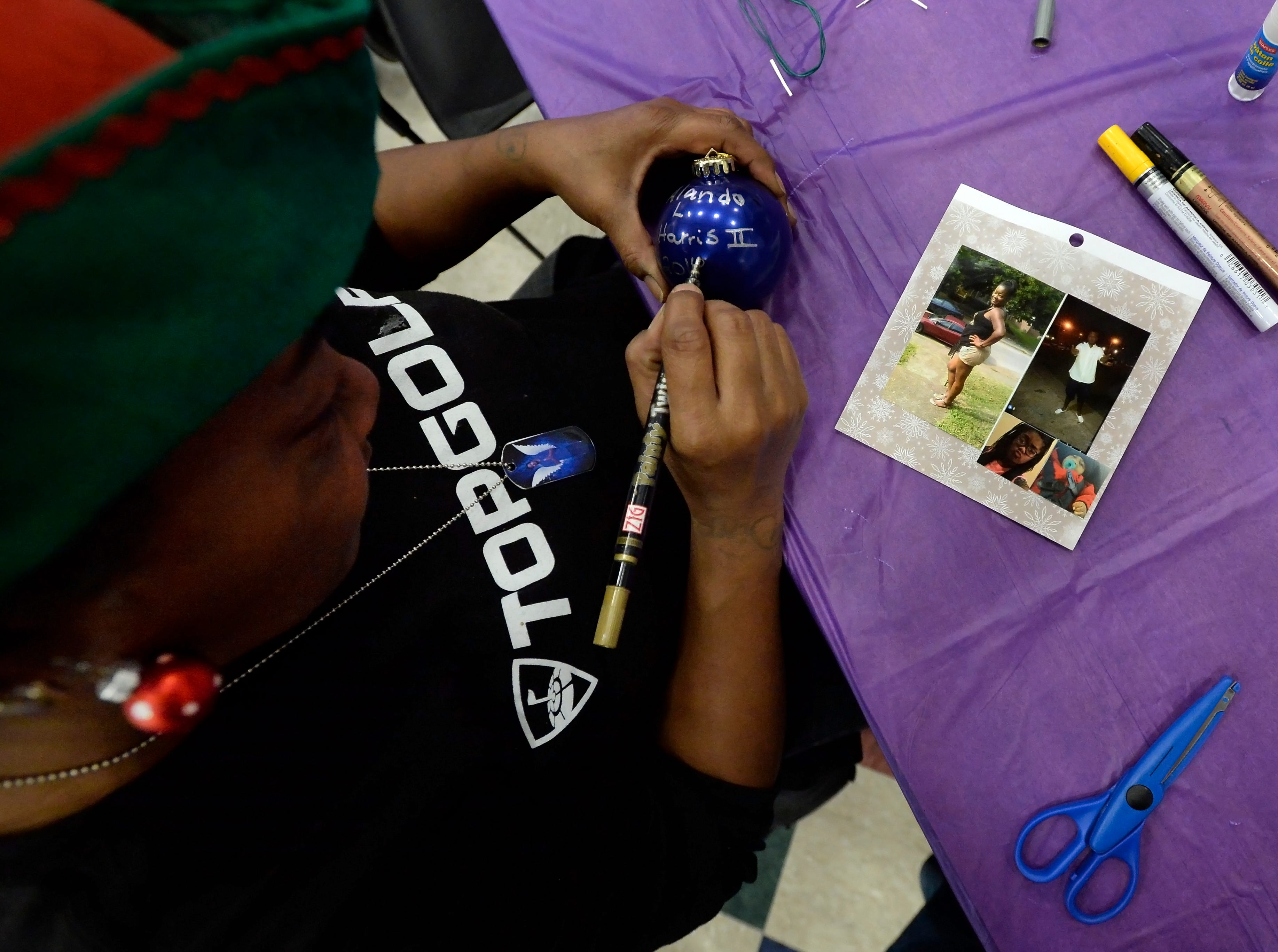 Cherrie Anglin is making a Christmas ornament in memory of her son, Alando Harris II, at the Metro Police Department's North Precinct on Tuesday, Dec. 11, 2018, in Nashville, Tenn. The Victim Intervention Program is a community outreach program through the police department.