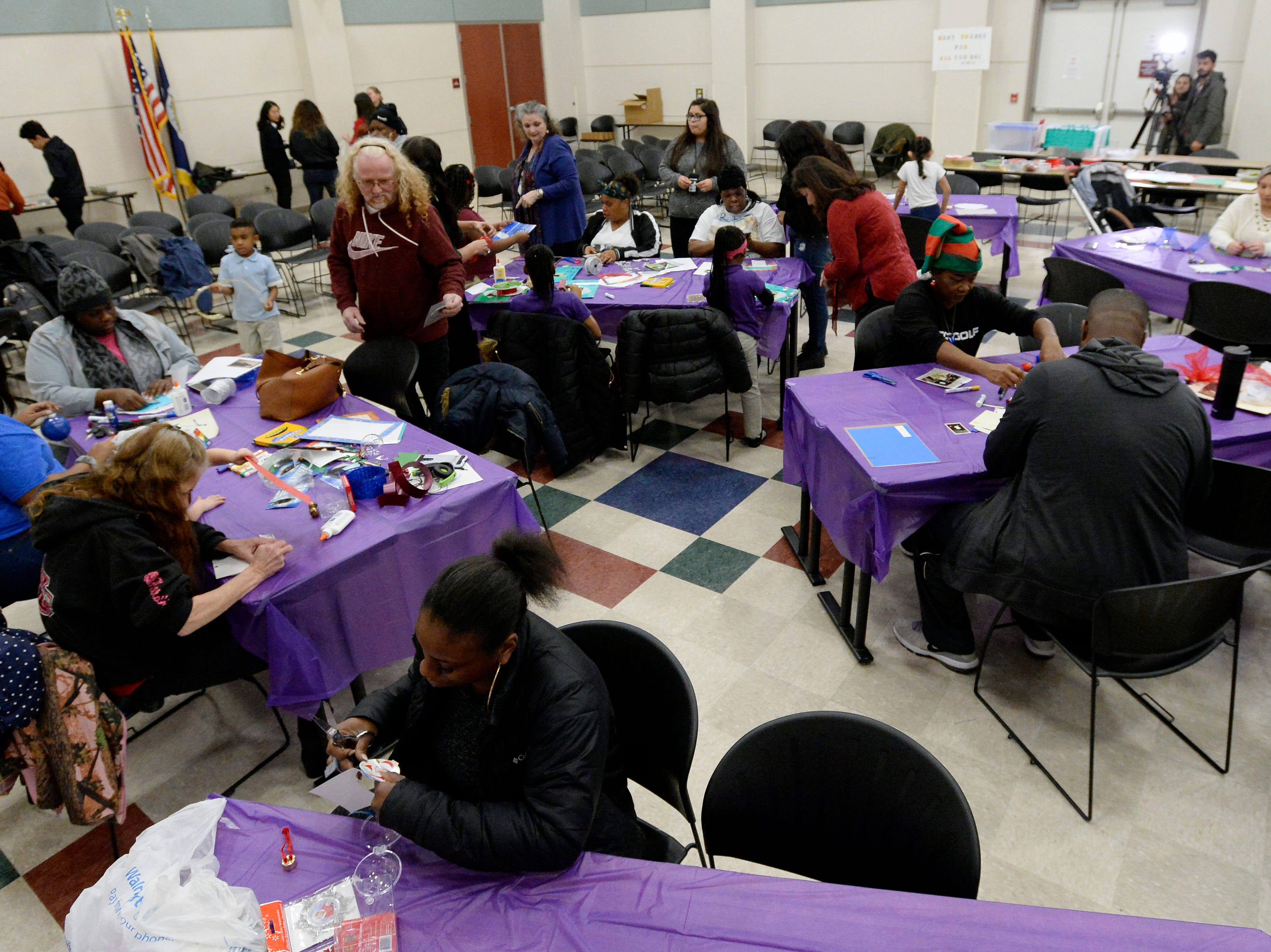Families who have lost loved ones in homicides make memorial Christmas ornaments at the Metro Police Department's North Precinct on Tuesday, Dec. 11, 2018, in Nashville, Tenn. The Victim Intervention Program is a community outreach program through the police department.