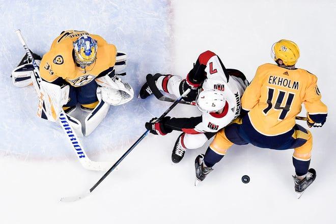 Nashville Predators goaltender Pekka Rinne (35) and defenseman Mattias Ekholm (14) defend against Ottawa Senators left wing Brady Tkachuk (7) during the third period at Bridgestone Arena in Nashville, Tenn., Tuesday, Dec. 11, 2018.