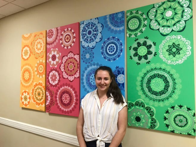 "Karina Pezeshkan stands in front of the work she created, ""A Colorful World."""