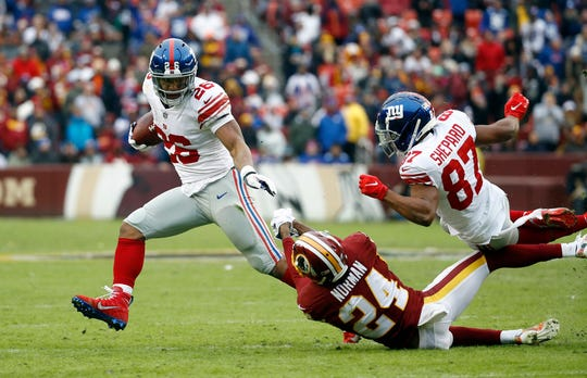 New York Giants running back Saquon Barkley (26) gets away from Washington Redskins cornerback Josh Norman (24) with Giants wide receiver Sterling Shepard (87) having thrown a crushing block during the first half of an NFL football game Sunday, Dec. 9, 2018, in Landover, Md.