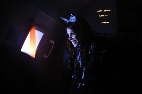 Children and families from Beth Israel Hospital, University Medical Center and Trinitas Hospital took a United Airlines from Newark International Airport to the North Pole for a visit with Santa on Wednesday, December 12, 2018. Flight attendant Fernanda Mariani peers out the window as the plane approaches the North Pole.