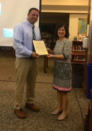 Chatham athletic director Bill Librera receives the proclamation to name the Indian Hills gymnasium for his grandfather from Ramapo-Indian Hills BOE President Jane Castor.