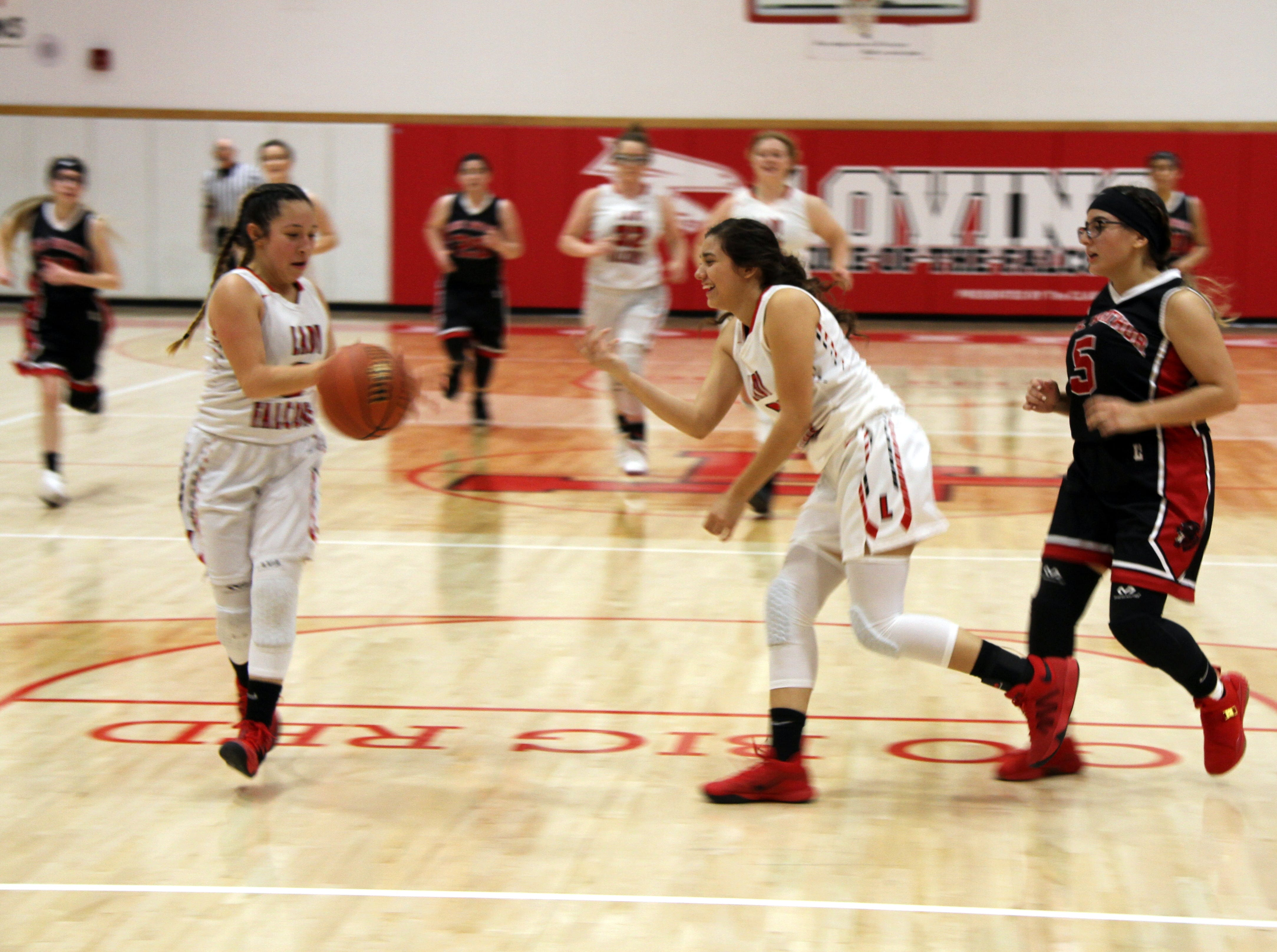 Frankie Hernandez (center) tosses the ball to Tiana Rodriguez (left) to complete a fastbreak during Tuesday's game against Lake Arthur. Loving won, 65-13.