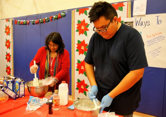 Regina BlueEyes, left, and Brian Lee prepare icing for gingerbread hogans during the family winter conference at the Shiprock Youth Complex on Wednesday in Shiprock.