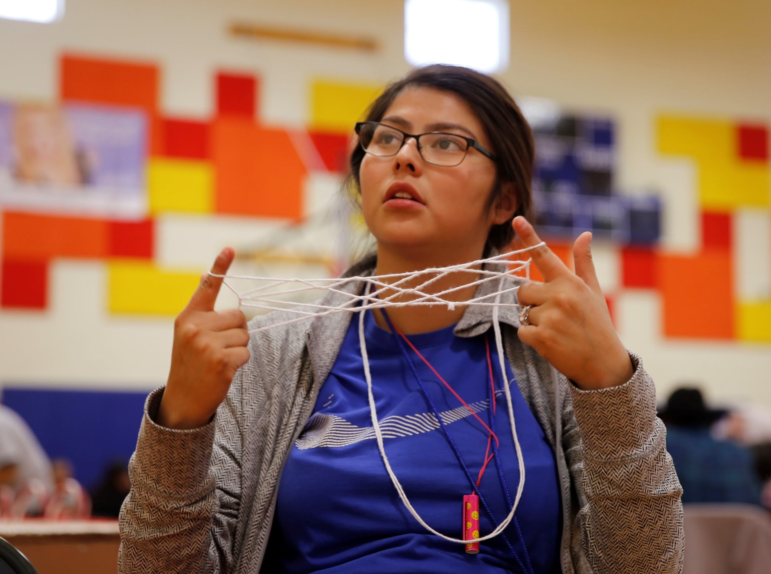 Audrey Sanchez follows instructions to create a Navajo string game design during the family winter conference on Wednesday at the Shiprock Youth Complex in Shiprock.